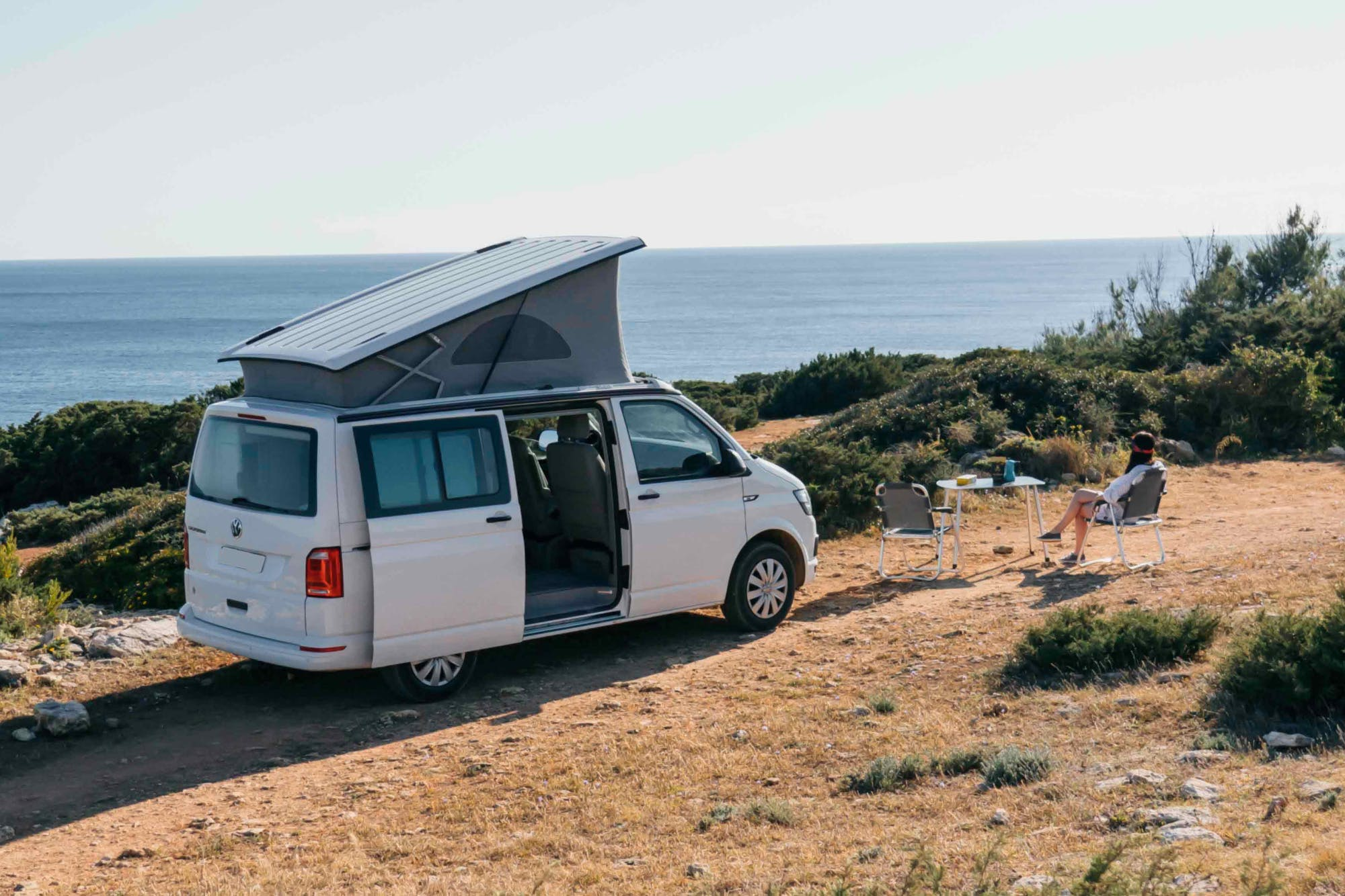 Woman sitting next to the VW California campervan admiring the landscape