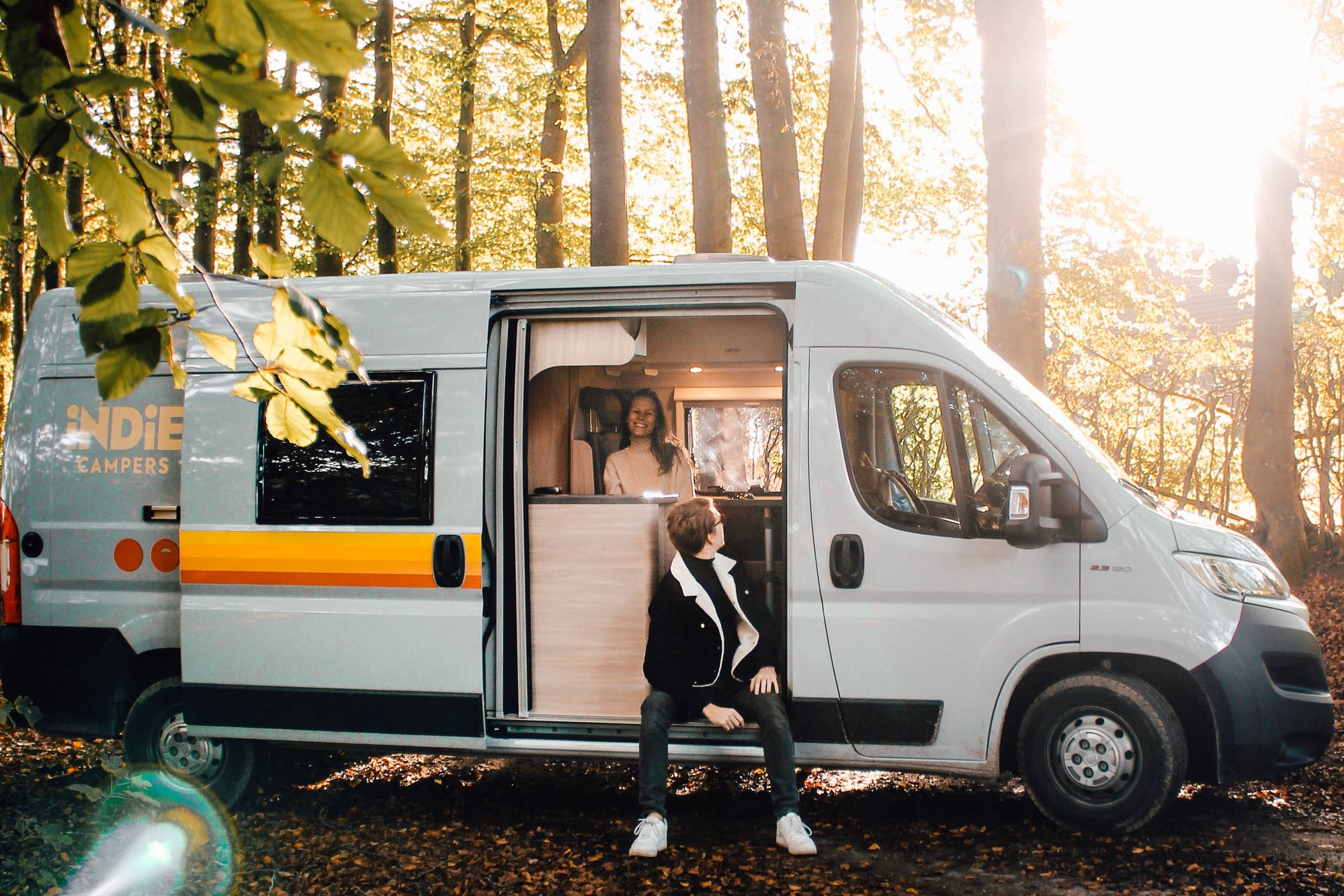 A couple enjoying living in a camper van, sitting with the door open in the woods.