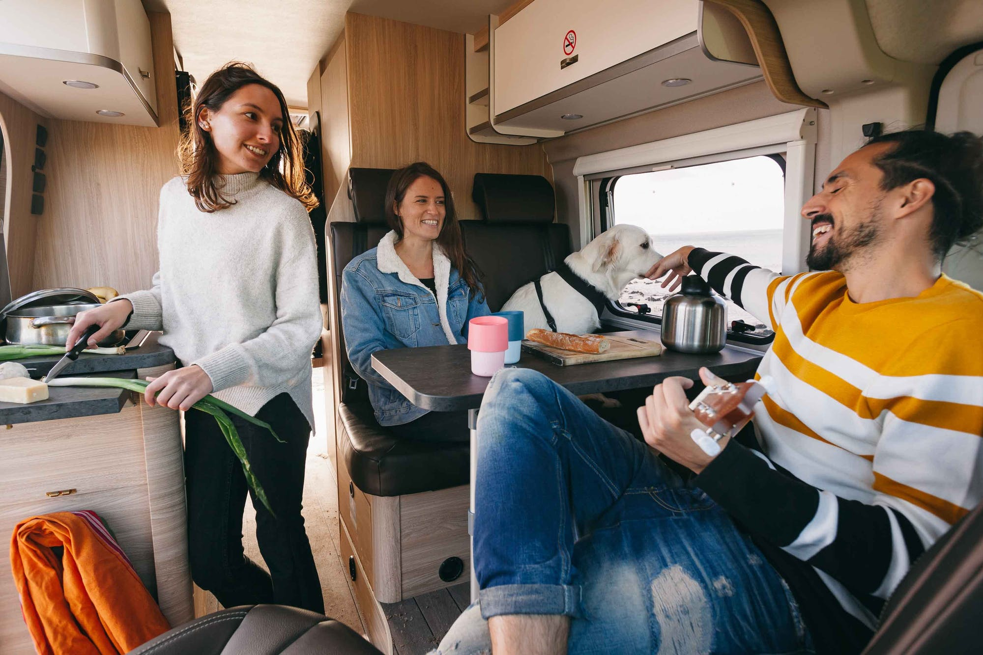 Three friends and a dog cooking inside the Indie Campers Nomad Model