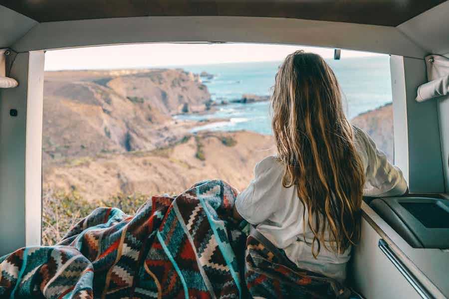 Girl sitting in a camper van looking outsite