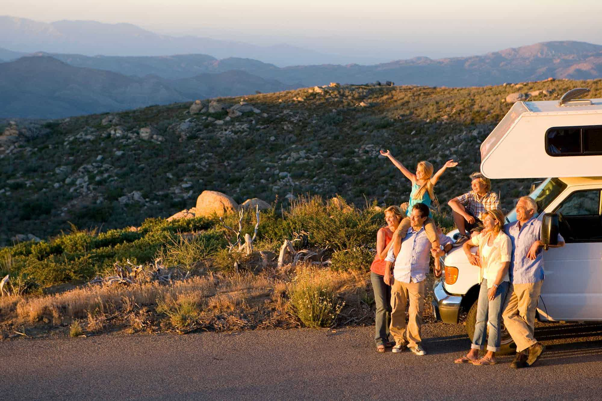 A big family watching sunset on the road in front of a campervan with mountains in the background