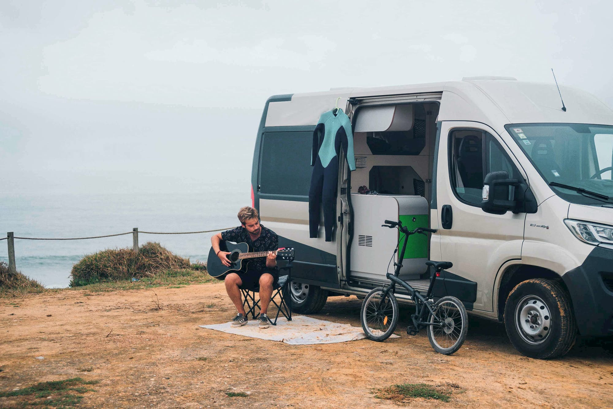 Man playing guitar next to the Active Model - Campervan Hire in Europe