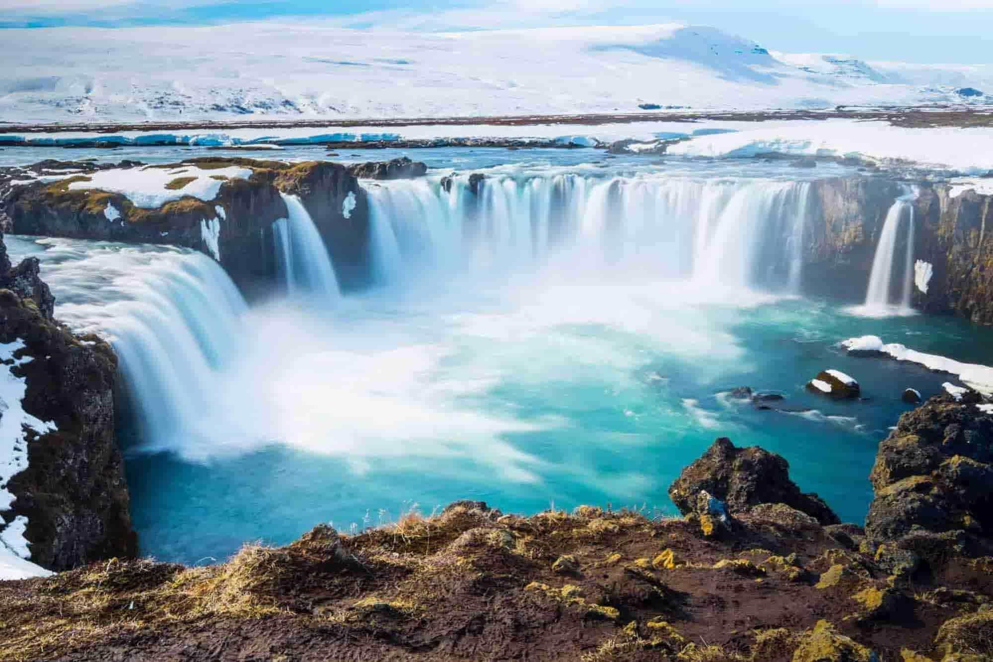 Ein Wasserfall mit Schnee im Hintergrund, eine der Landschaften des Island Roadtrips