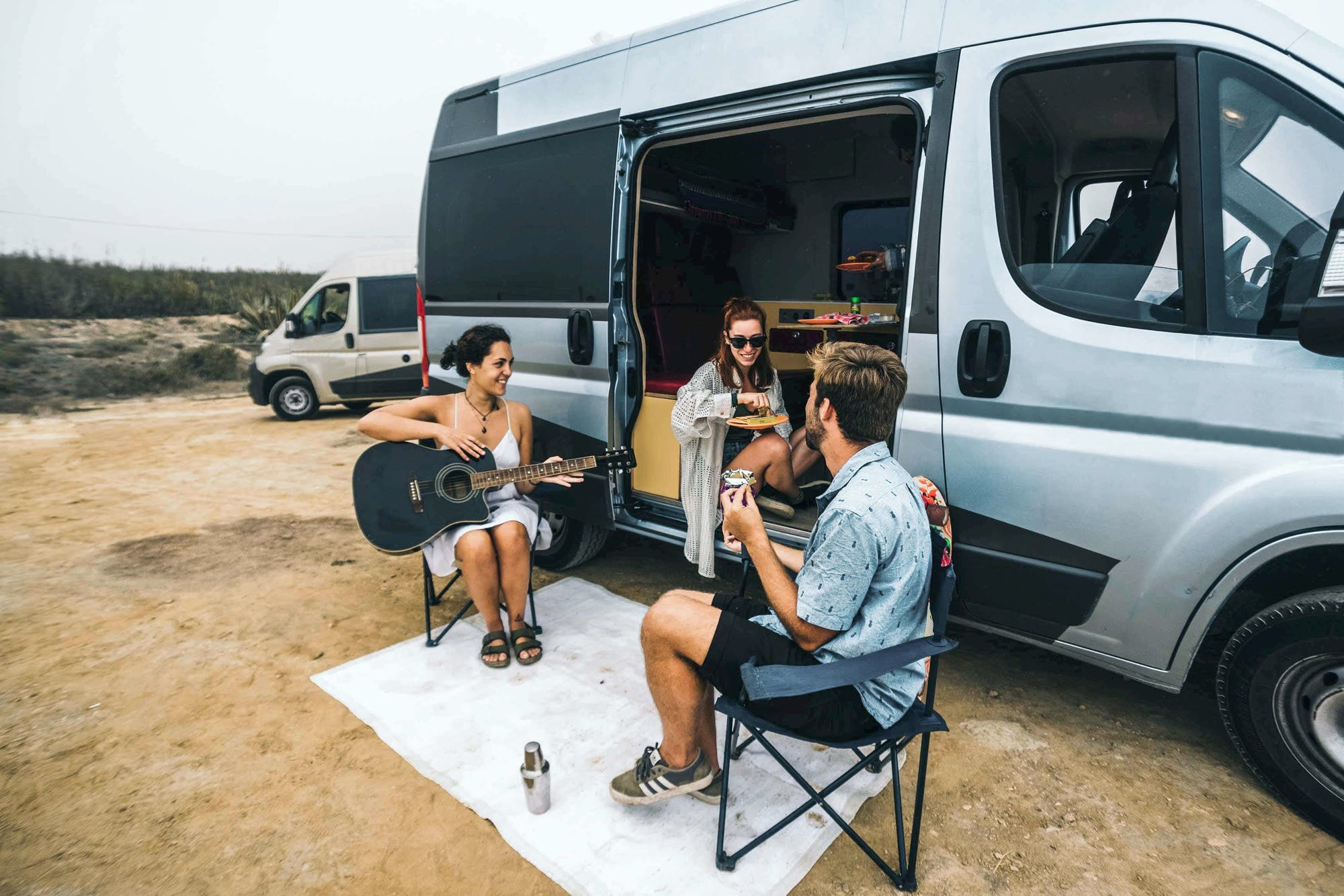 Friends outside the Sporty campervan playing guitar and having fun