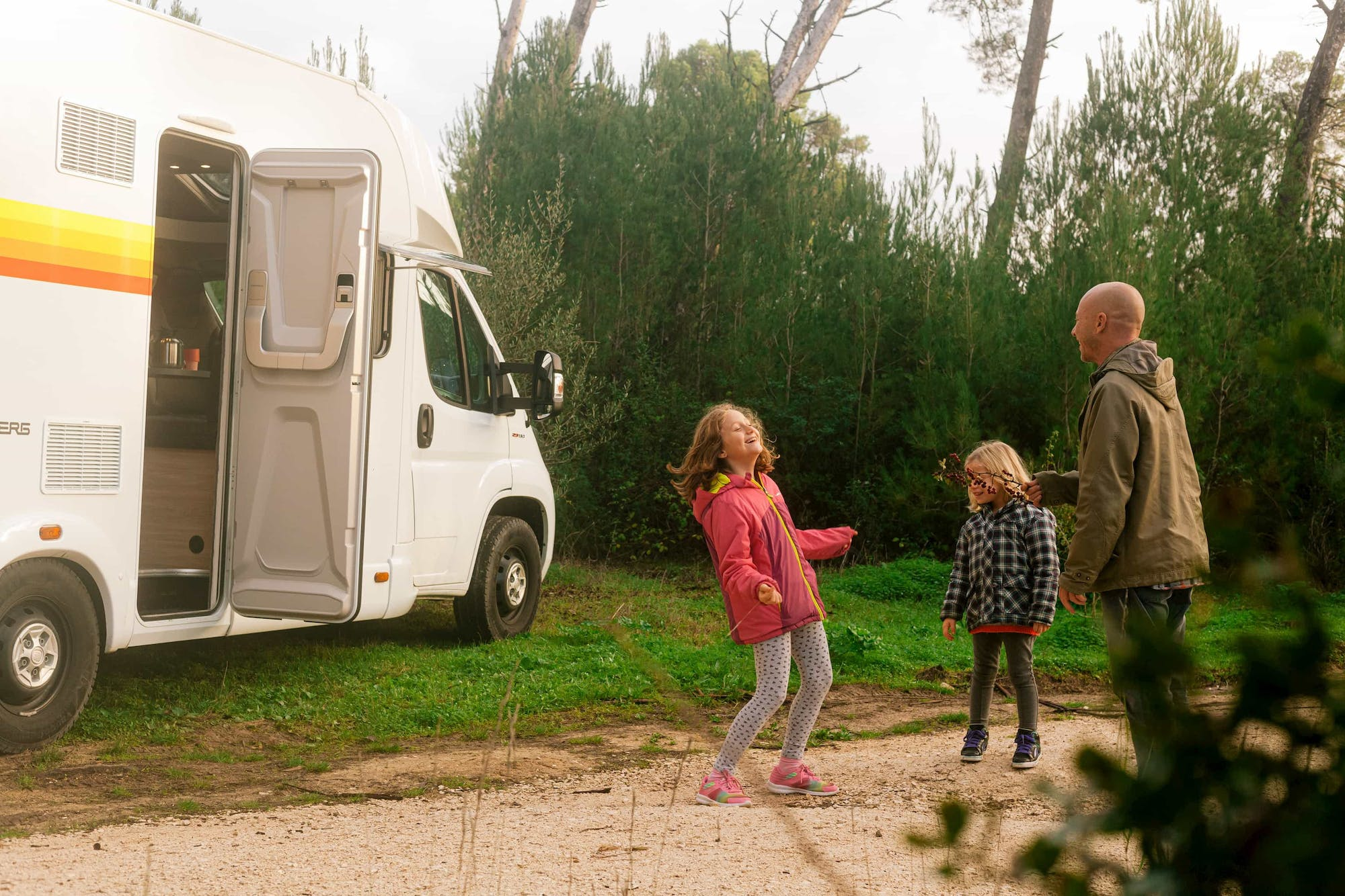 Family playing outside next to the Atlas campervan