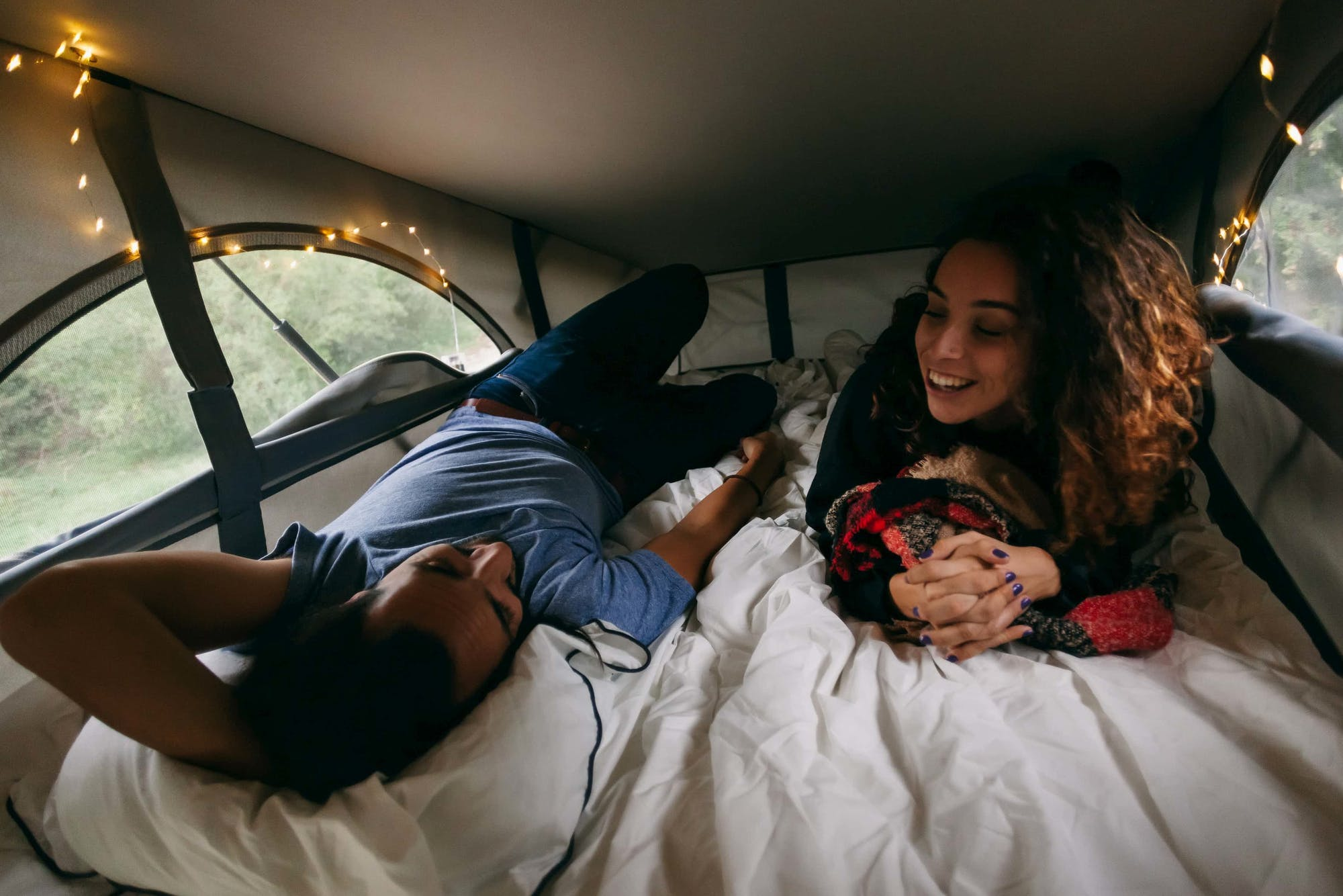 Couple on a bed inside the VW California's tent