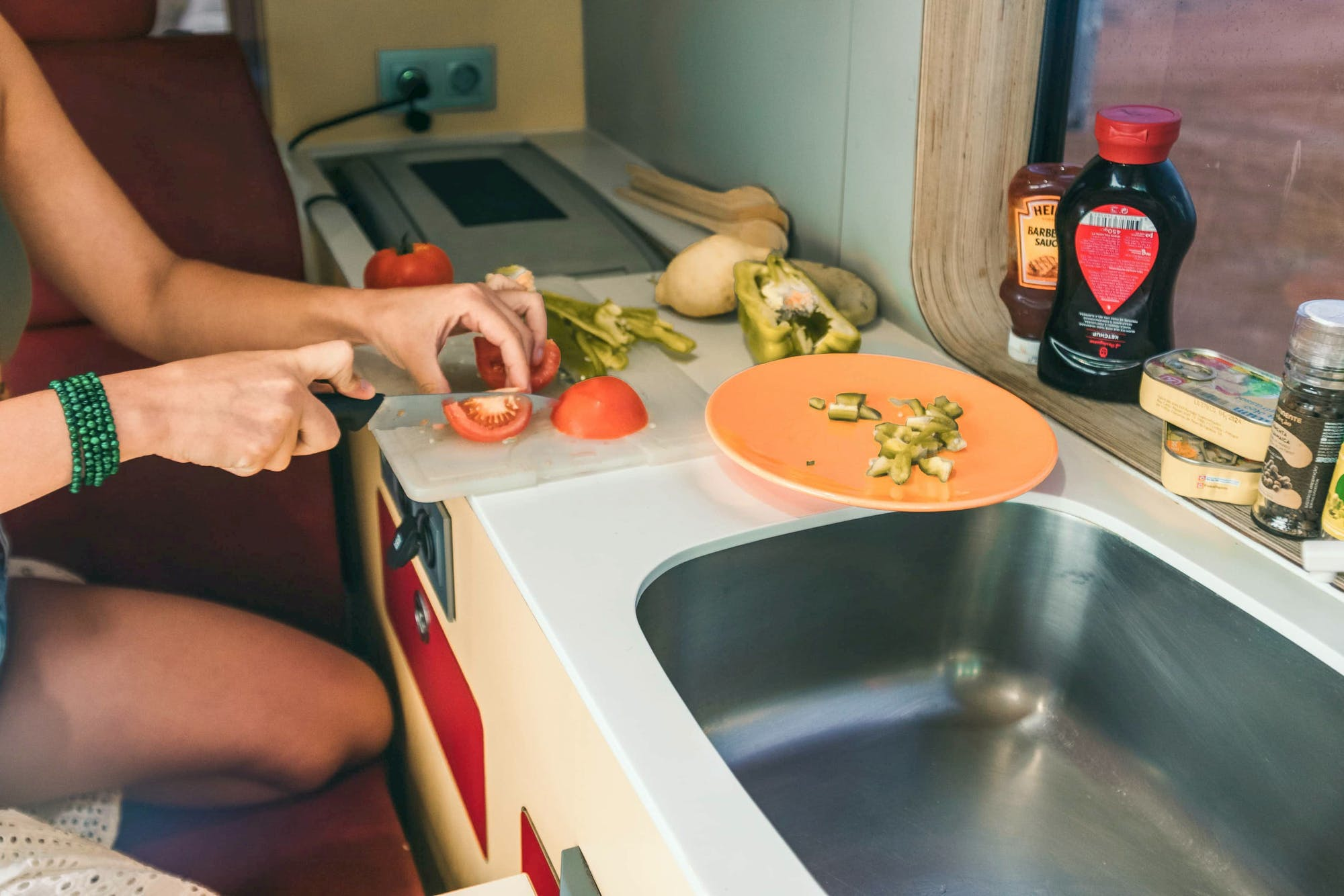 Woman's hand cooking inside the Sporty campervan