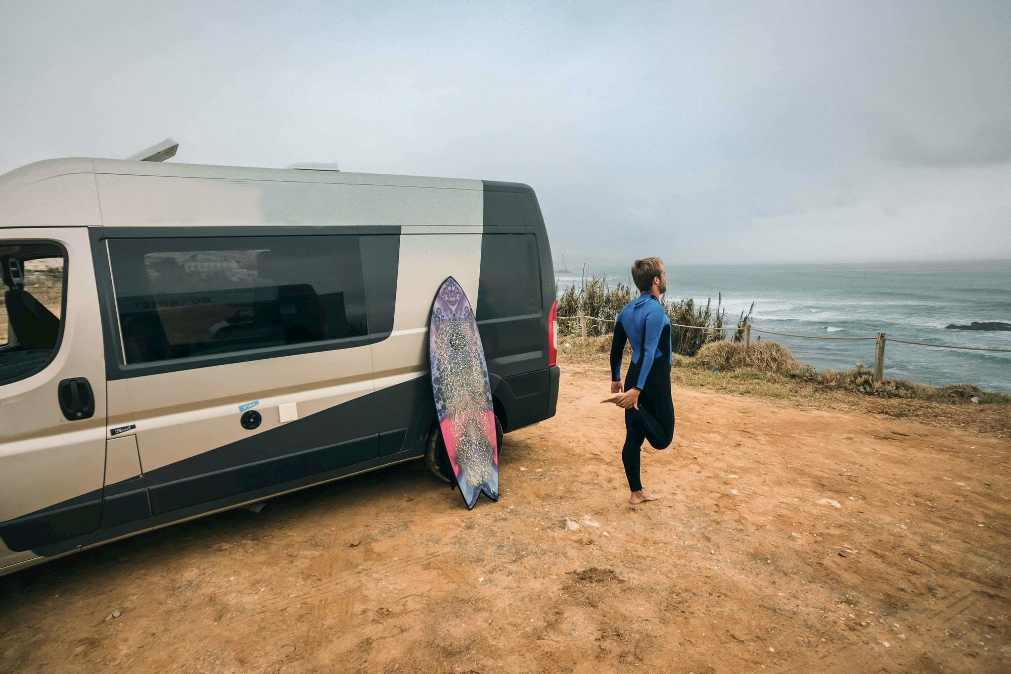 Man stretching next to the campervan Active Model from Indie Campers