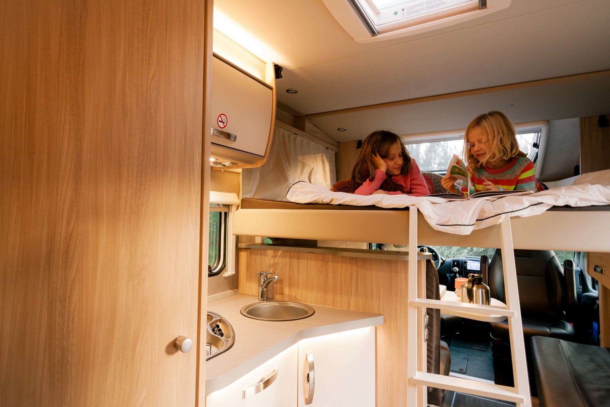 Two kids playing on the double bed inside the Atlas Model