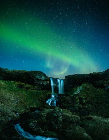 Northern lights over a waterfall