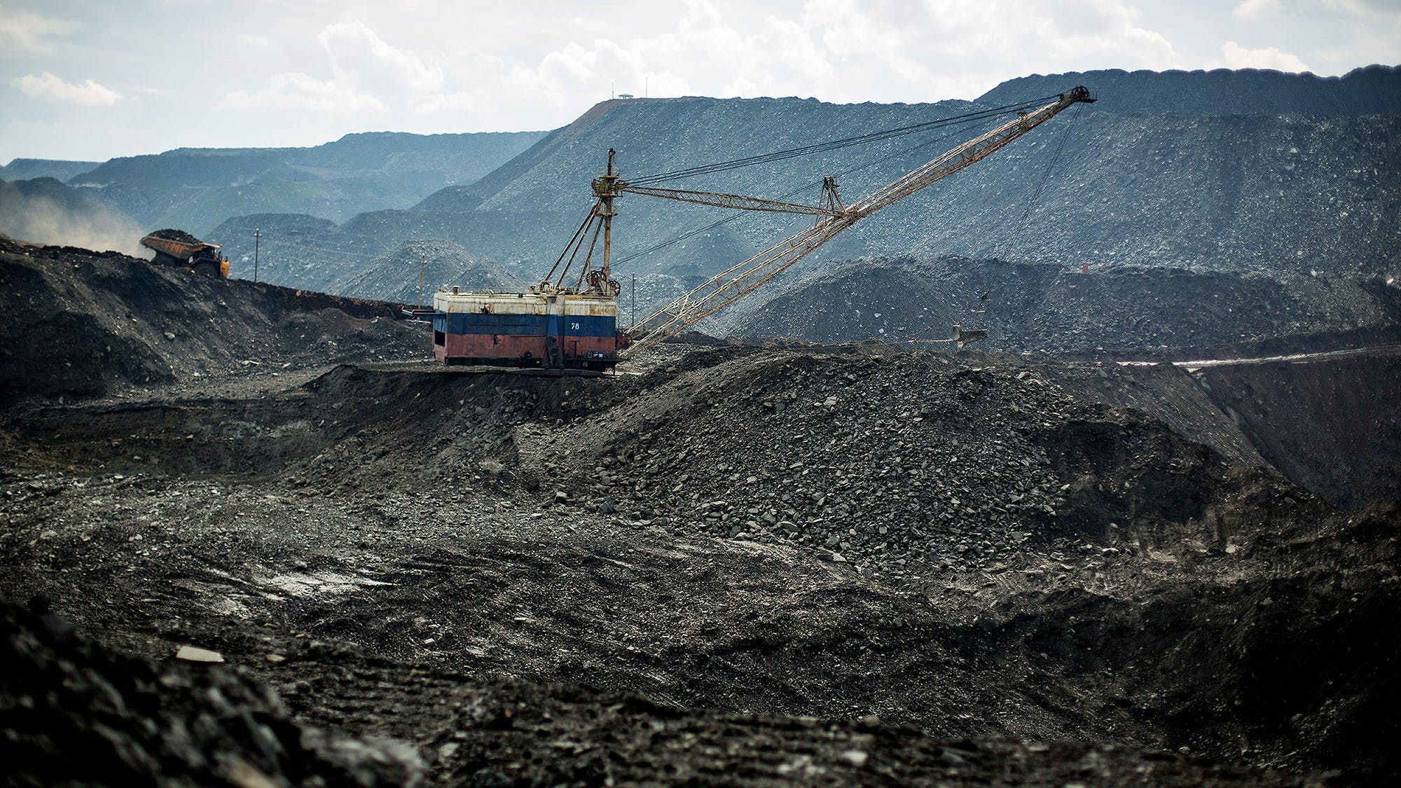 A coal mine stretches into the distance like an open wound in the Earth.