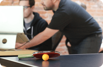 Ionic founders Max Lynch and Ben Sperry looking at computers with an in-focus ping-pong table with a dormant ball and paddle in the foreground