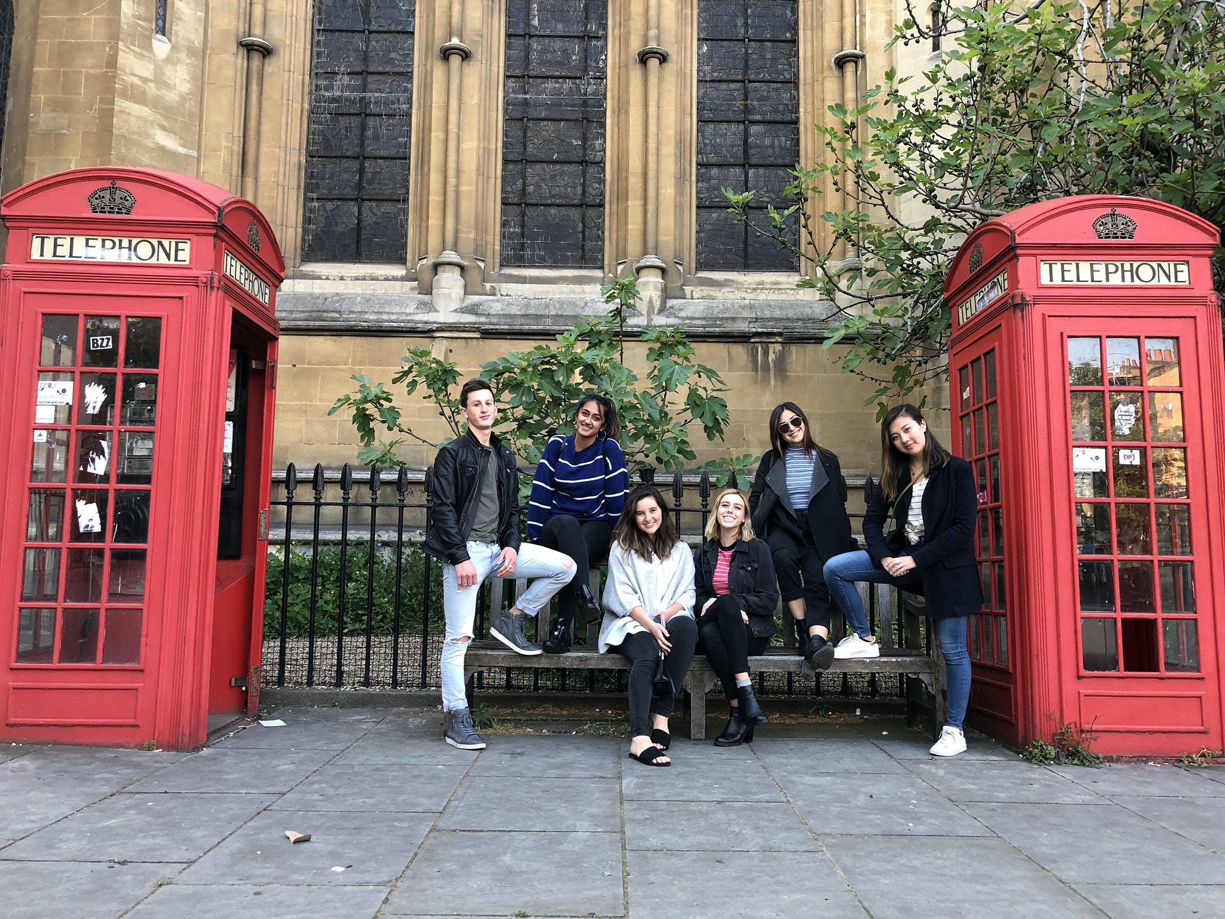 A group of students take a photo between two telephone booths in London