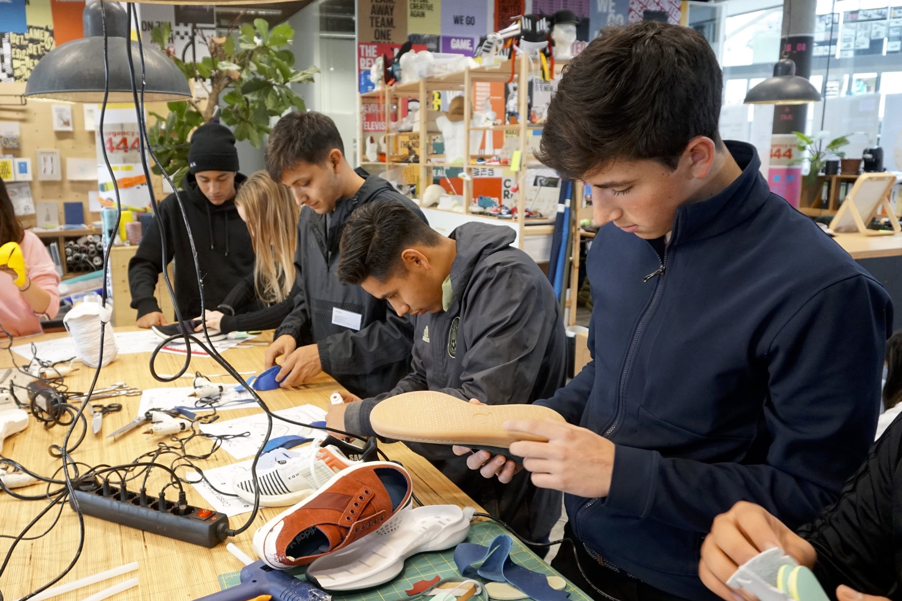 Male students standing around workshop table making shoe prototypes