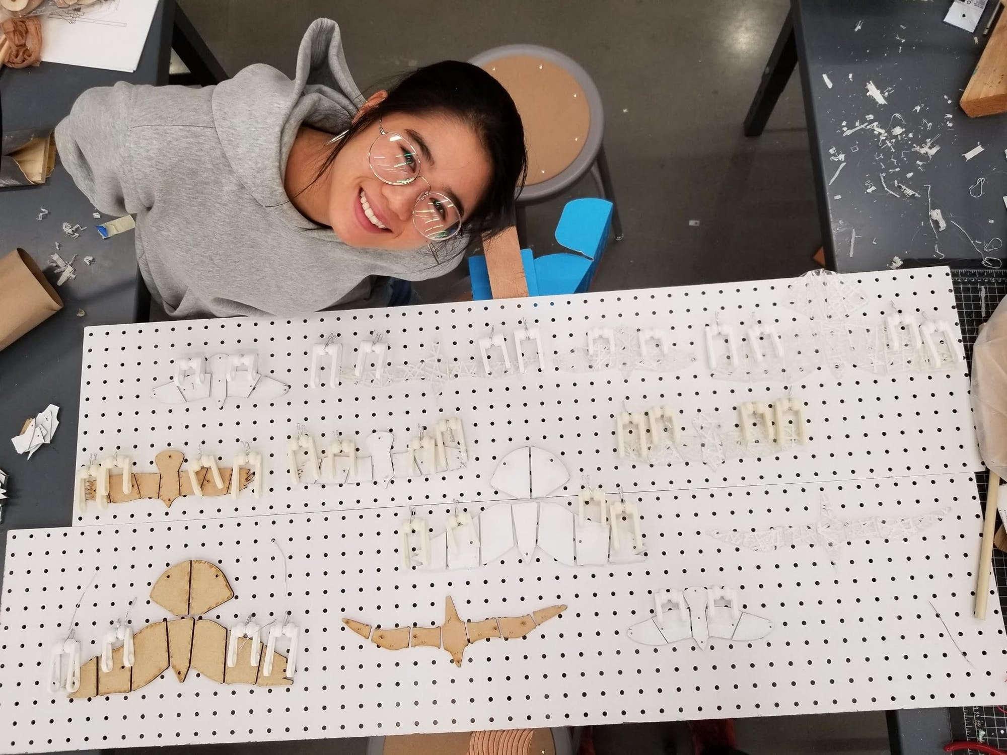 A young woman smiles up at a camera next to woodworking parts attached to a pinboard