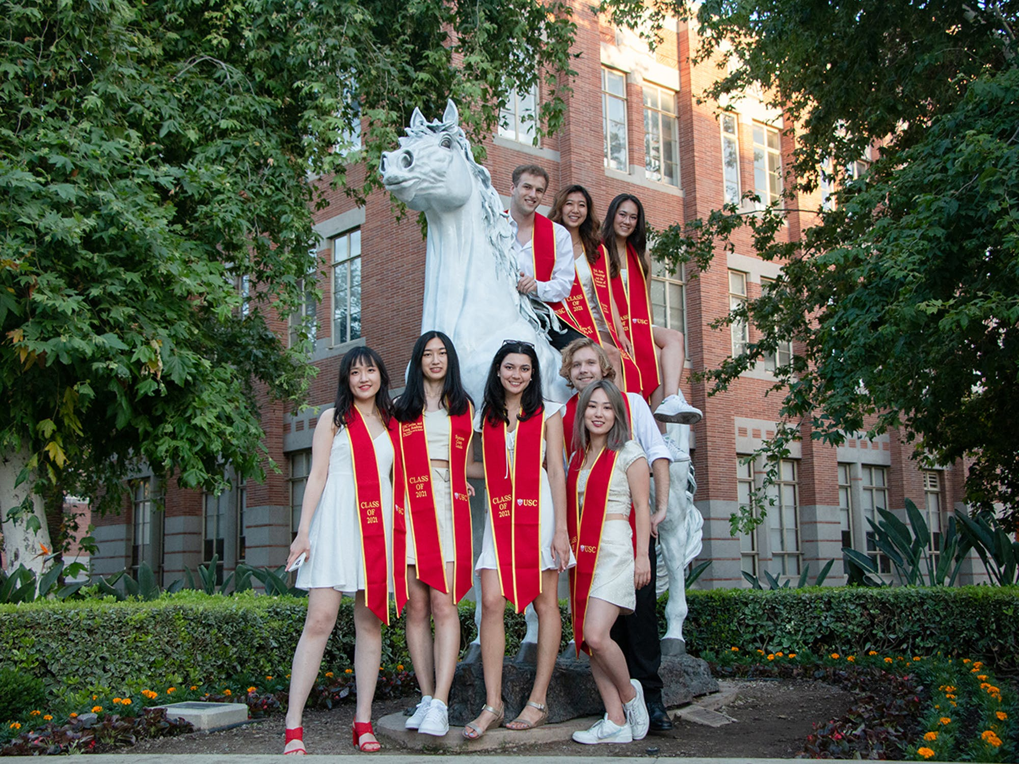 Graduating students wearing red sash standing by horse statue