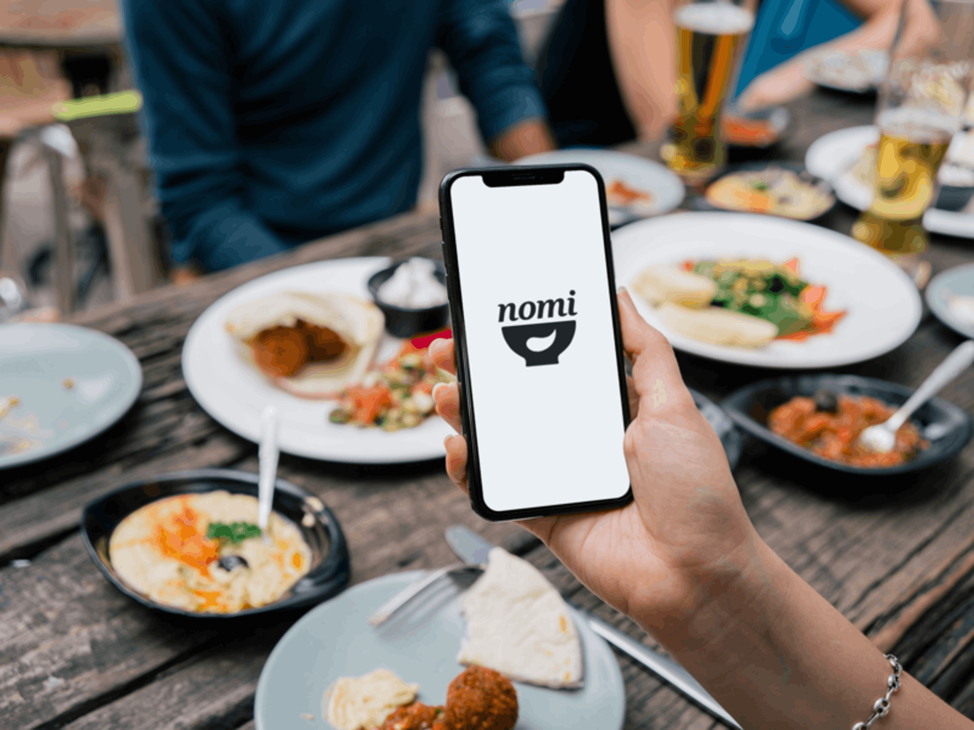 A woman holds her iPhone over a dinner table. The iPhone reads nomi