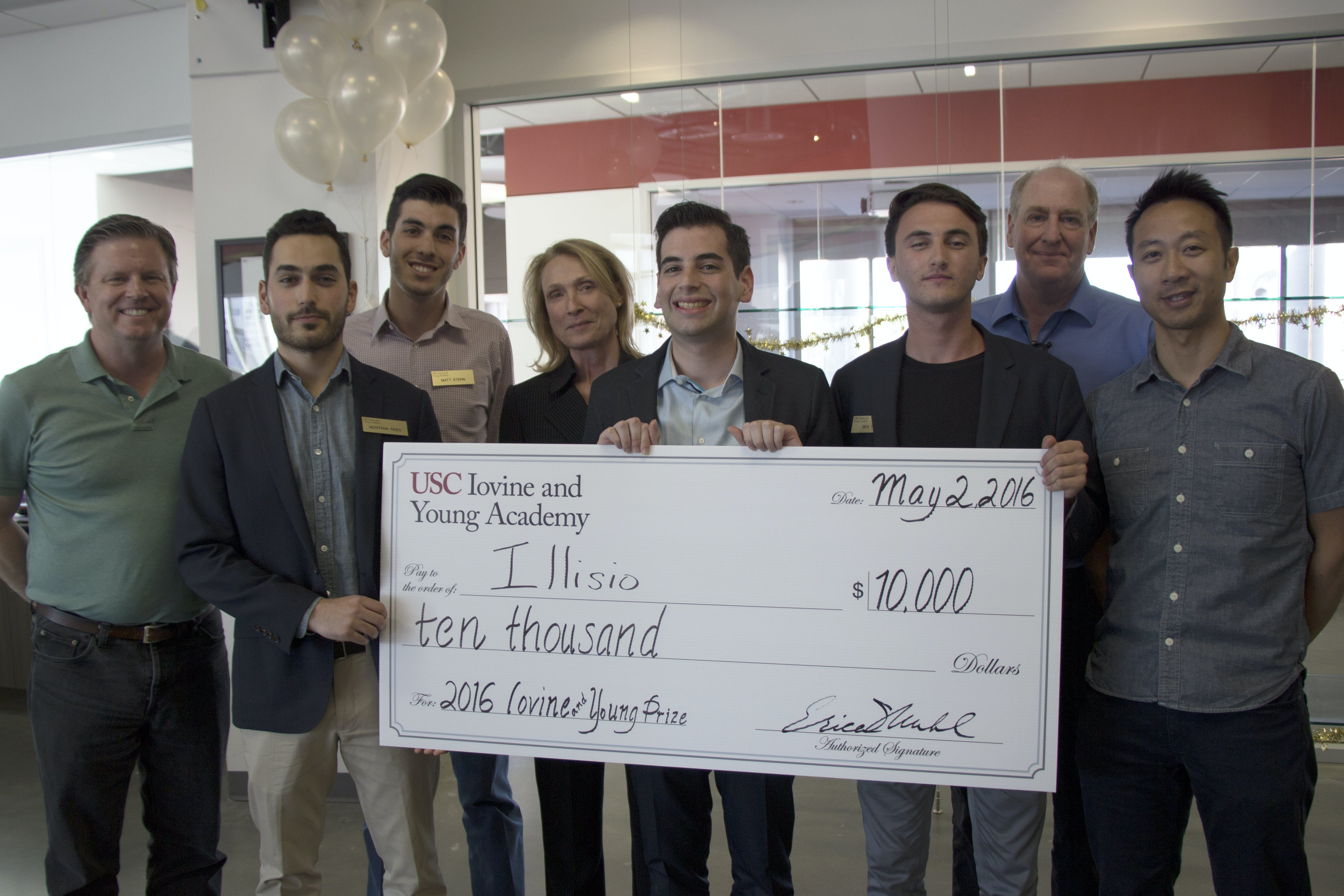 Group of male students hold giant check