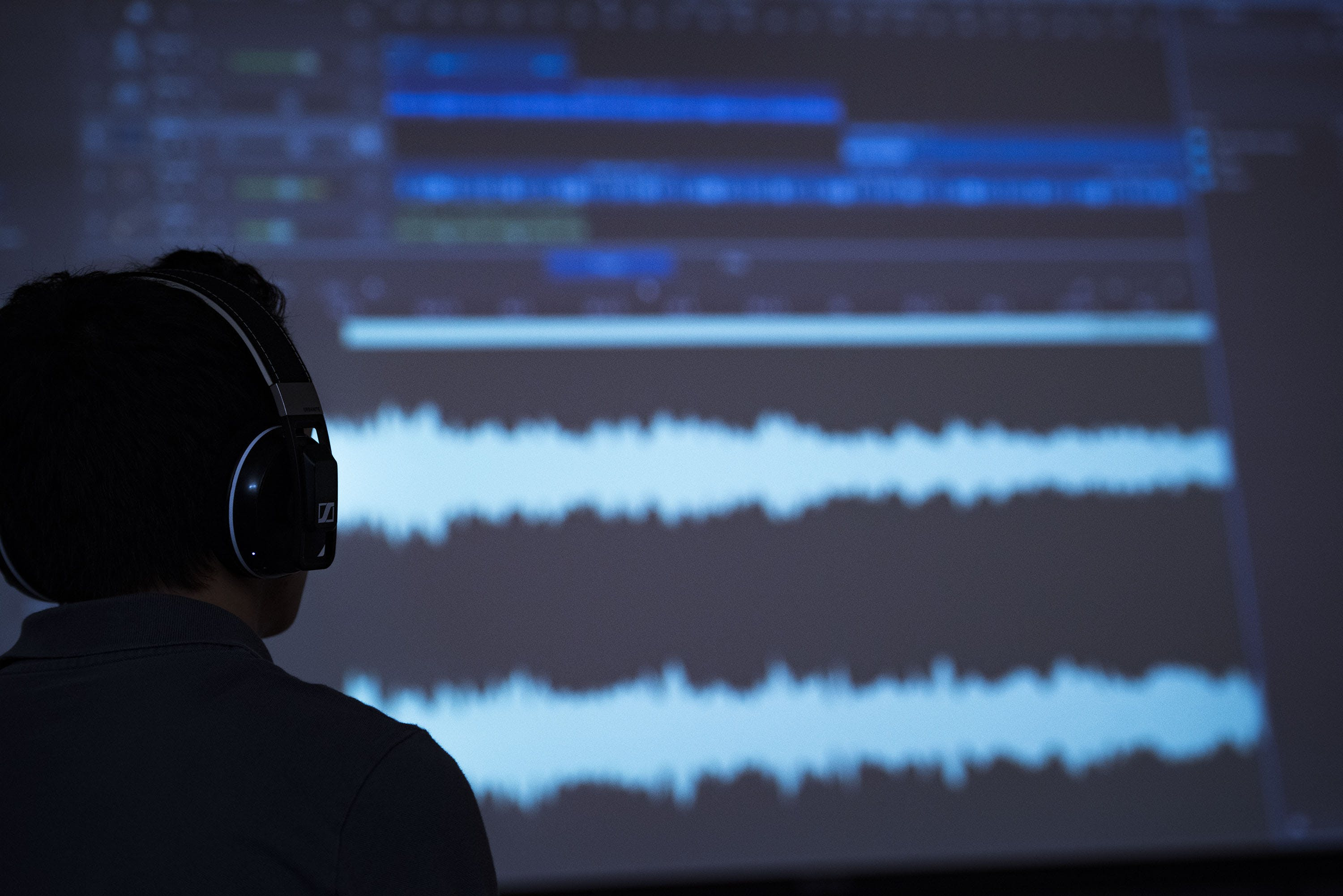 A student with headphones listening to an audio file