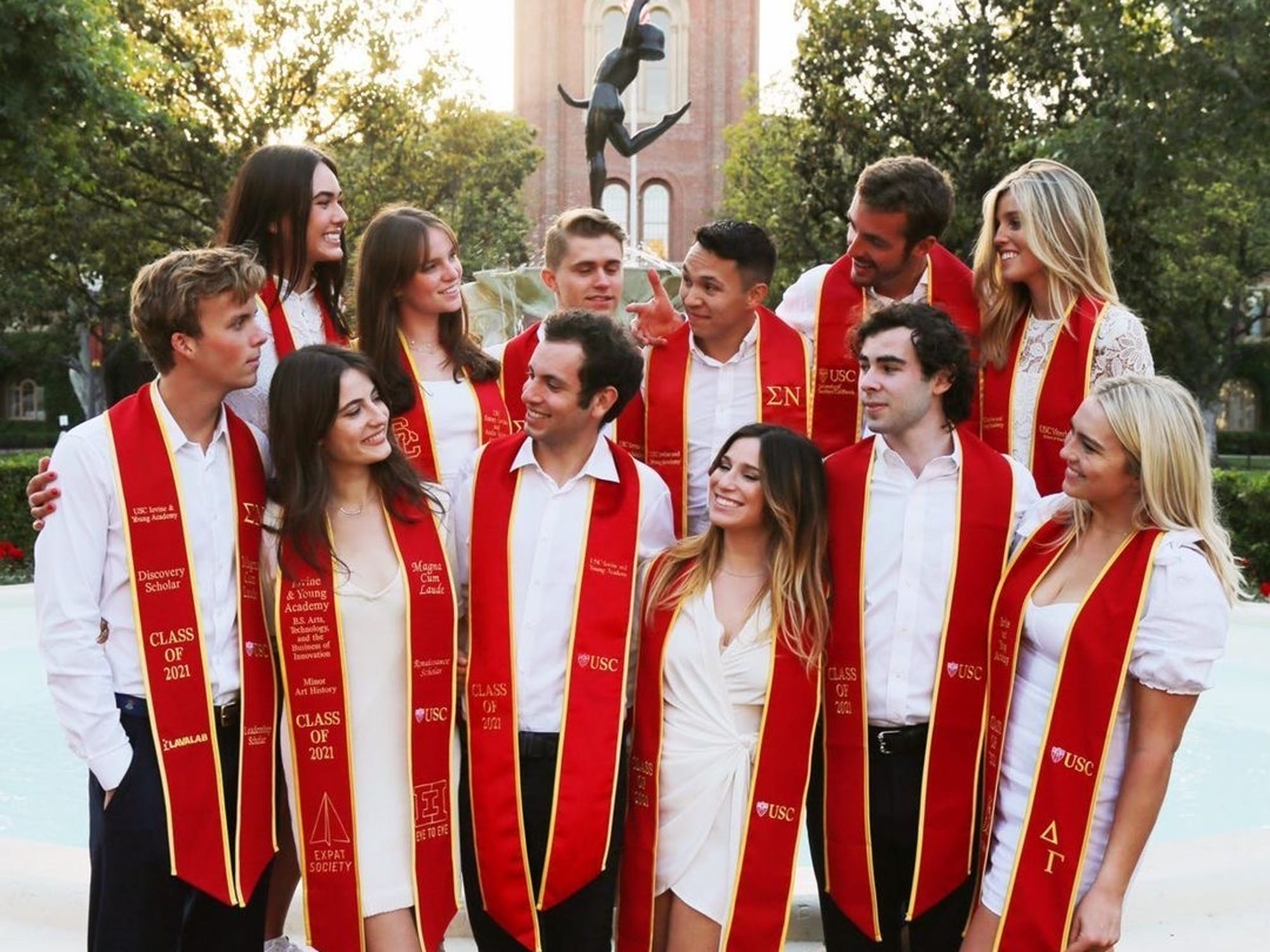 Group of graduating students wearing white and red sashes