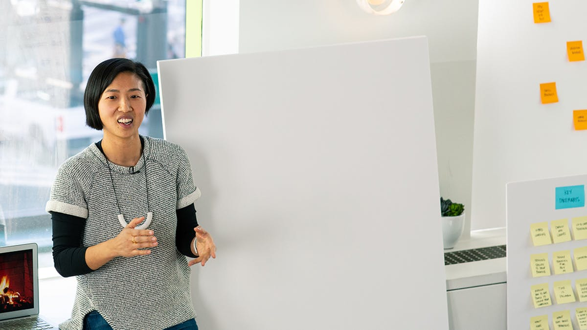 Female lecturer standing by white board and post-it notes