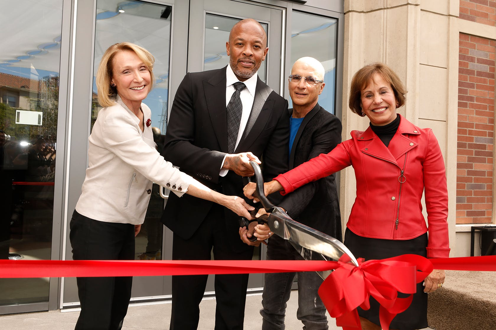 2 males and 2 females hold giant scissors poised to cut giant red ribbon