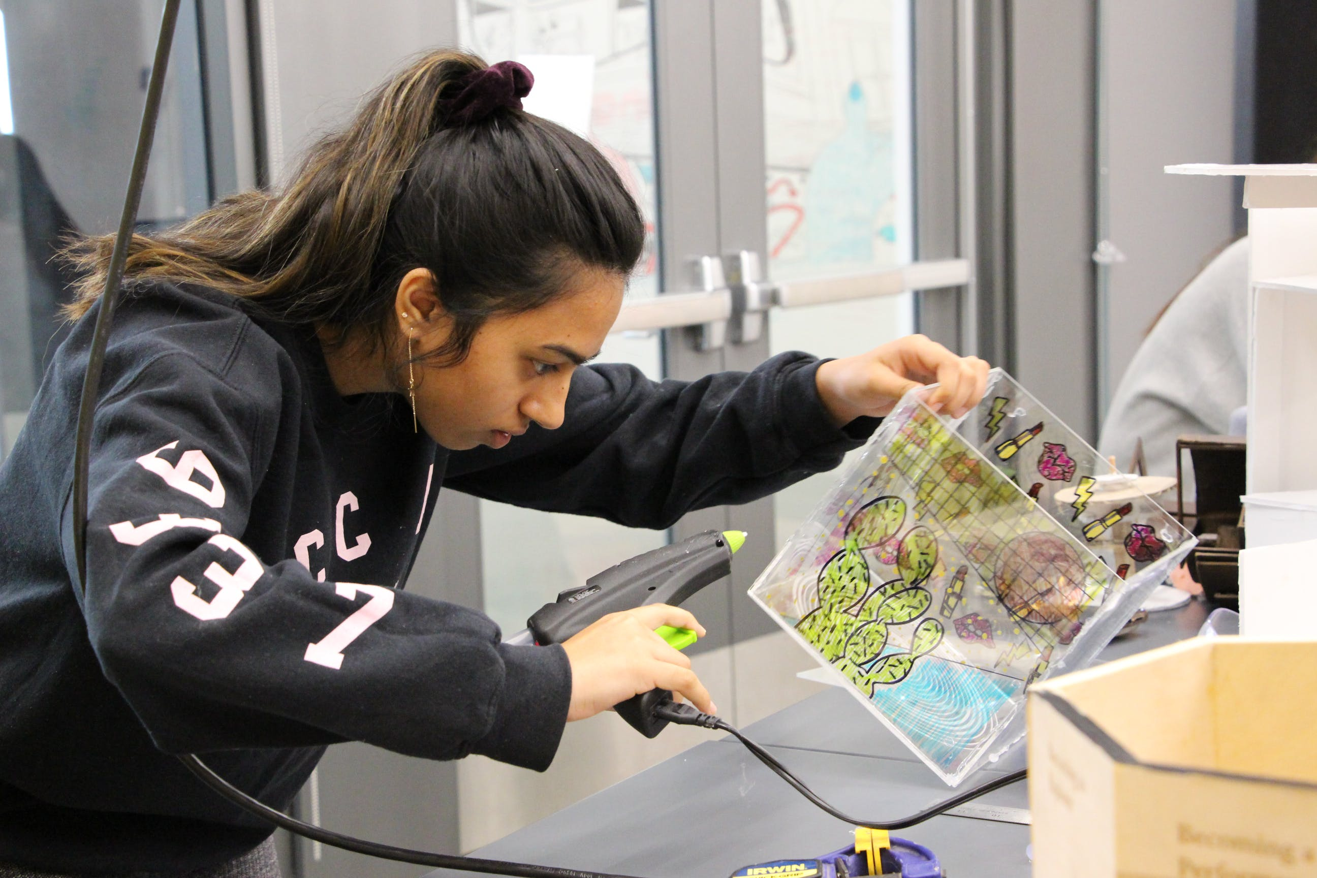 A student making art using a clear box