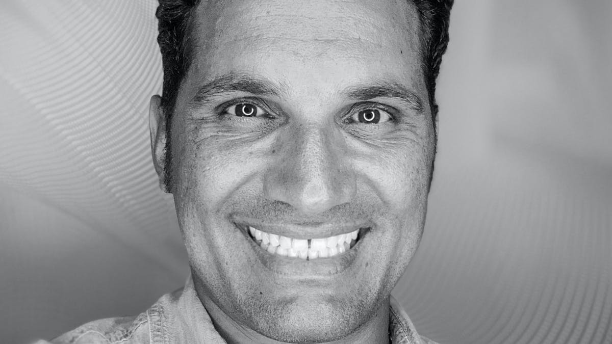 Black and white headshot of smiling male