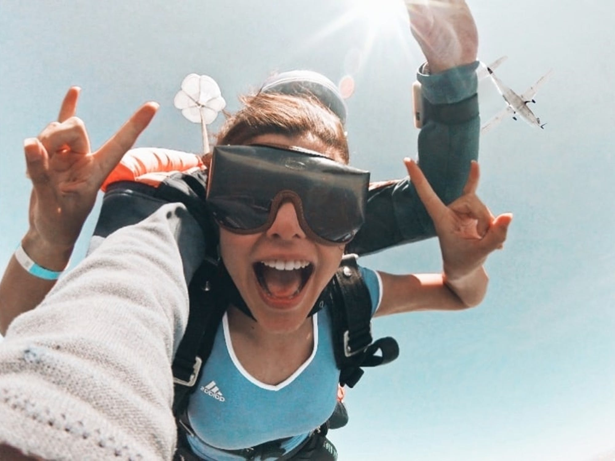 A young woman throws up horns while tandem-skydiving through the air. A plane flies past in the background above