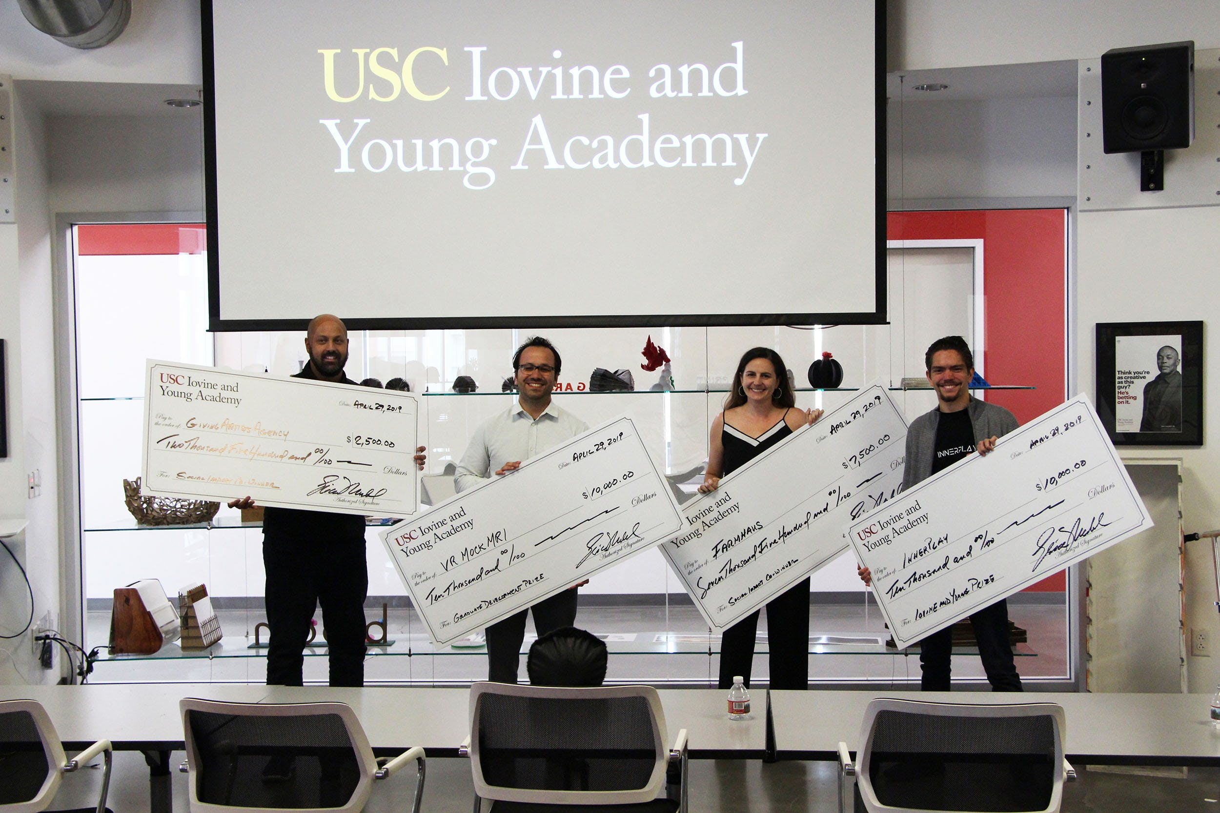 4 students each holding giant check