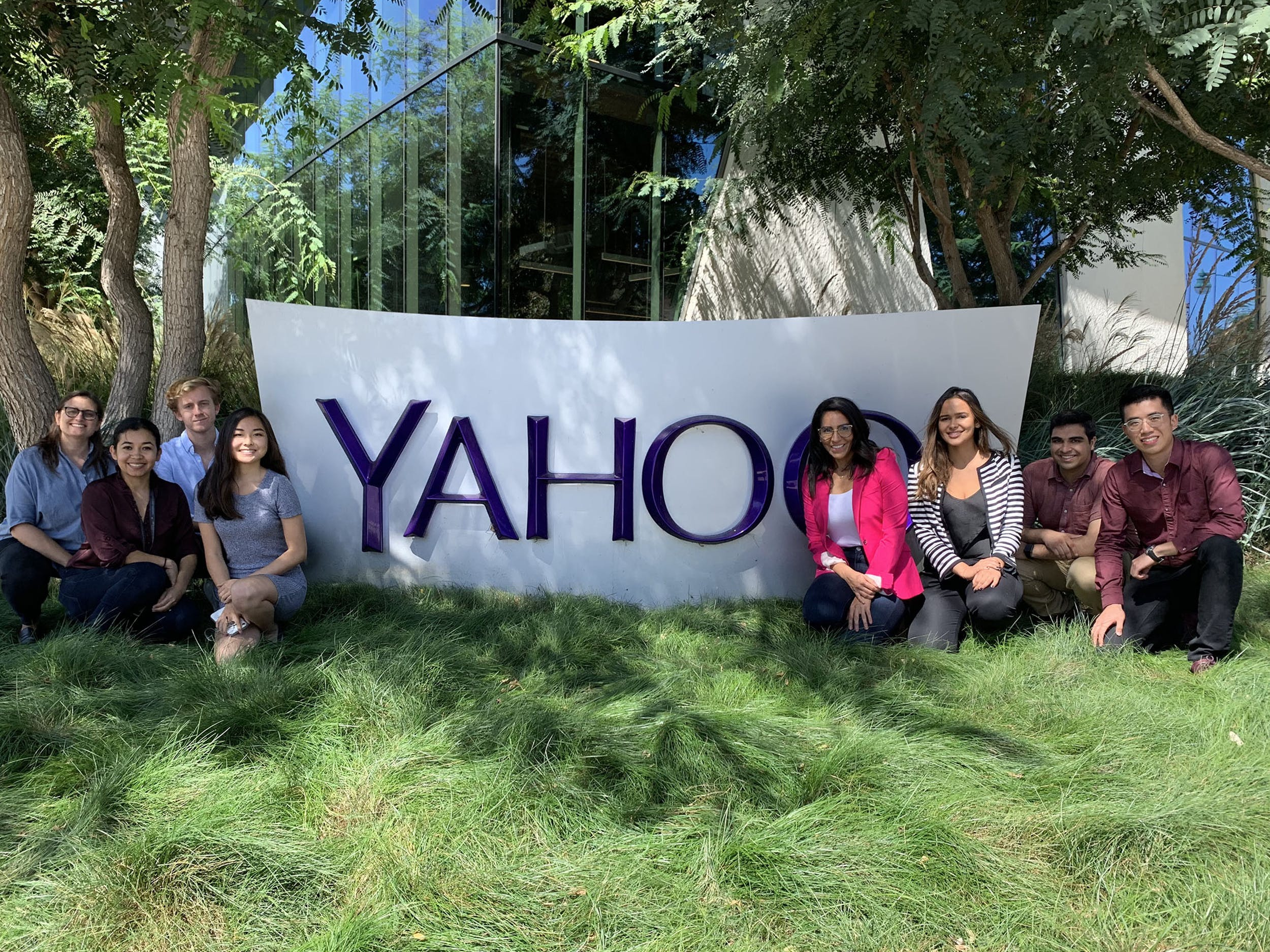 A group of students pose in front of a YAHOO sign