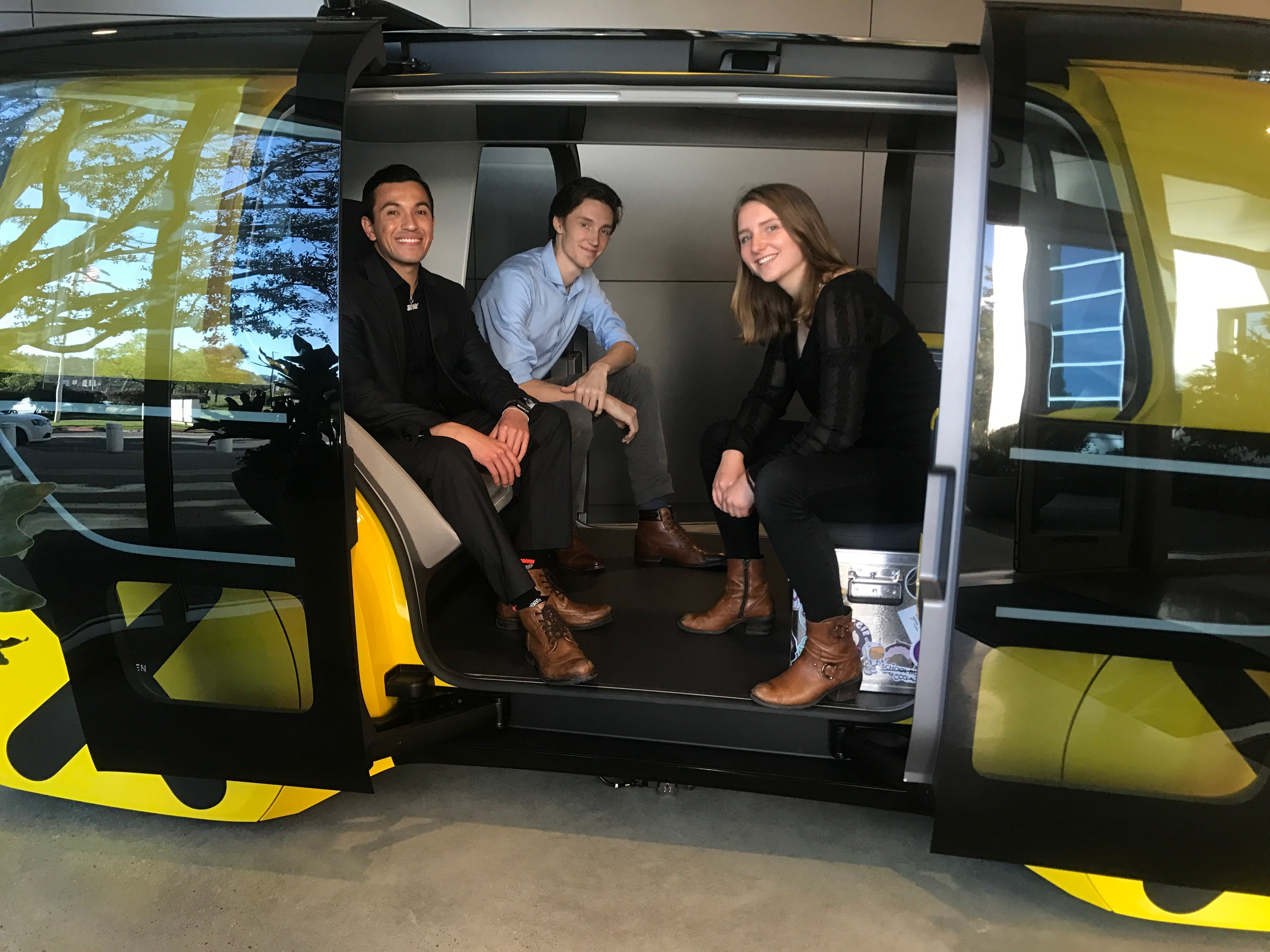 Three students sitting in yellow train with open door