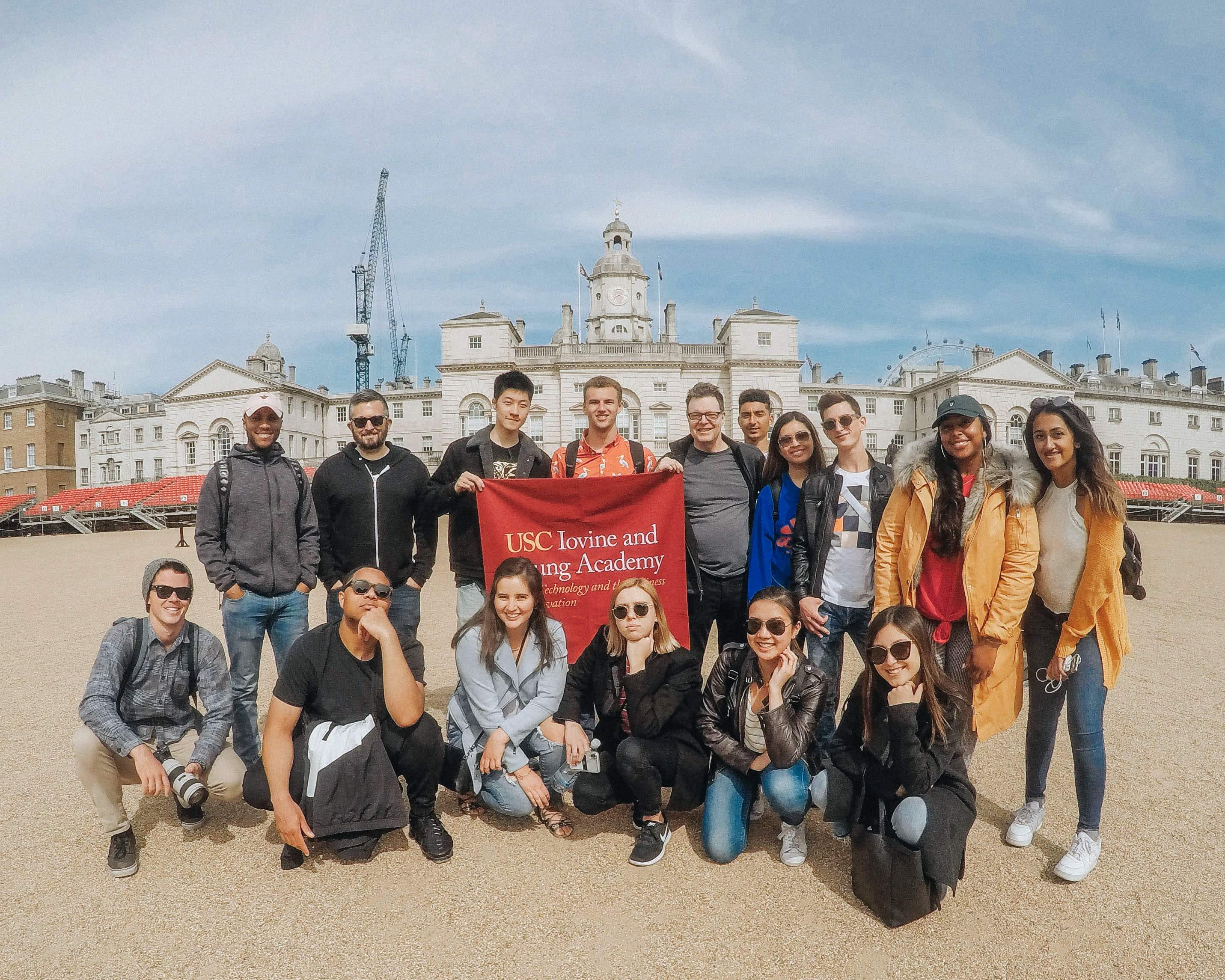 A class takes a photo in London while holding a USC IYA banner