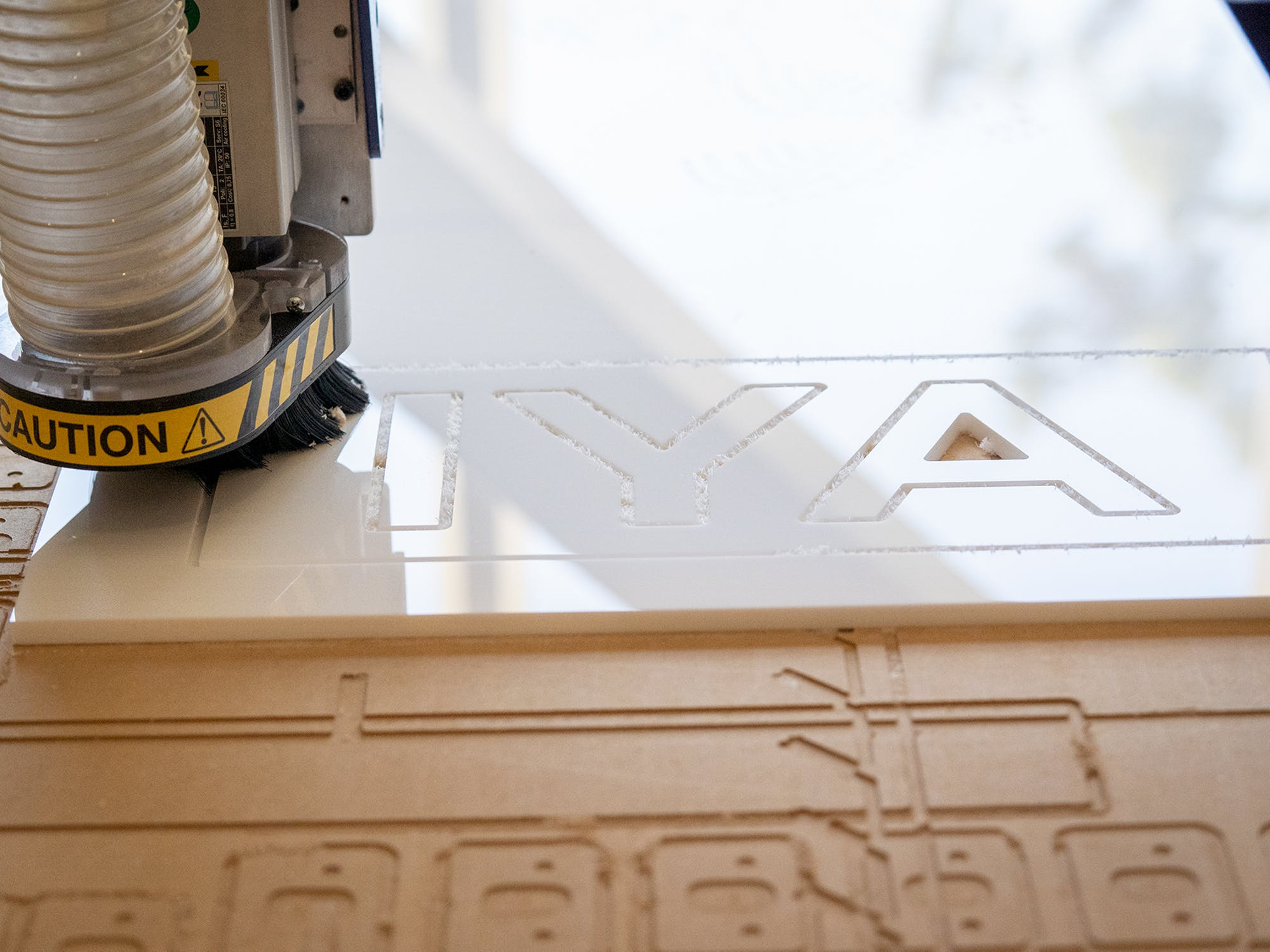 Machine etching letters on white plastic sheet