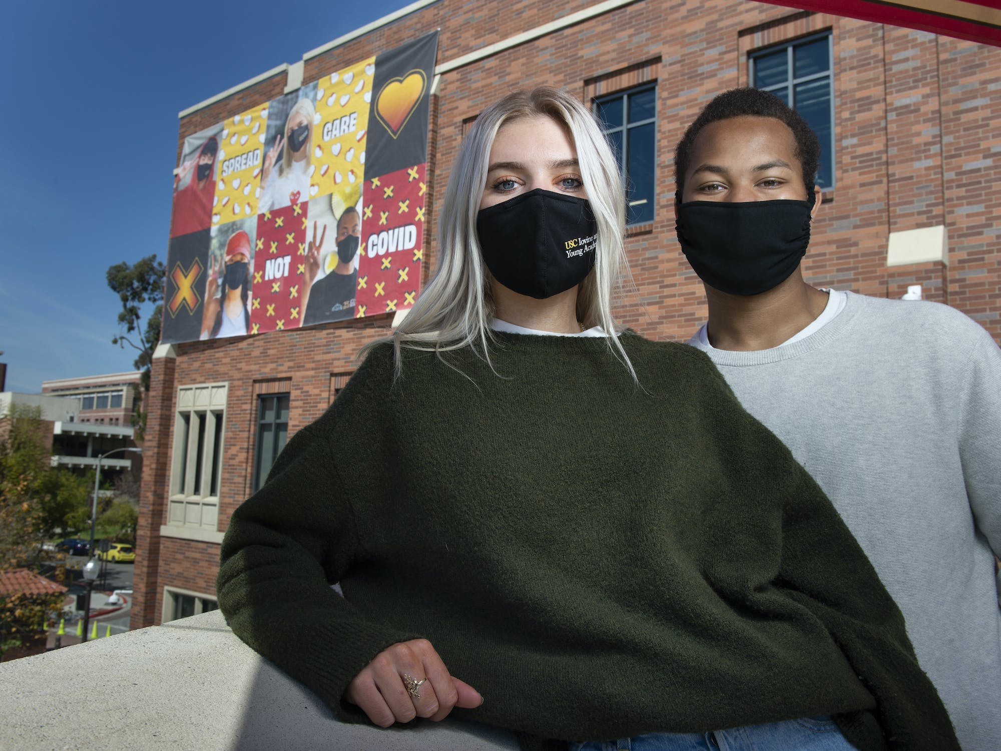 Two students wearing masks in front of building