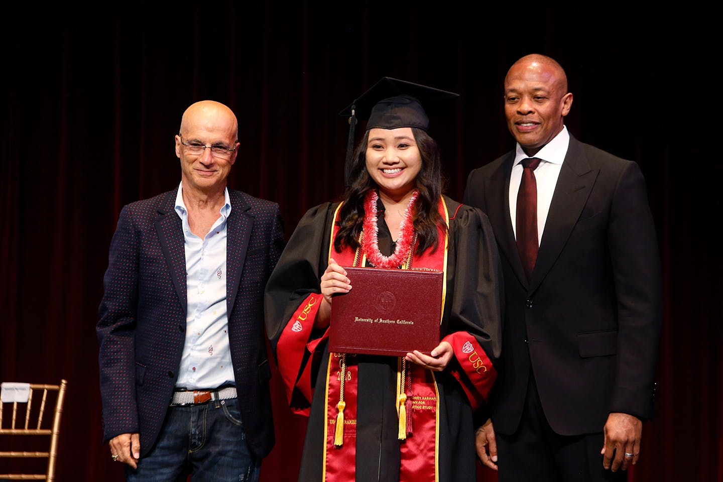 Two men pose with graduating student holding diploma