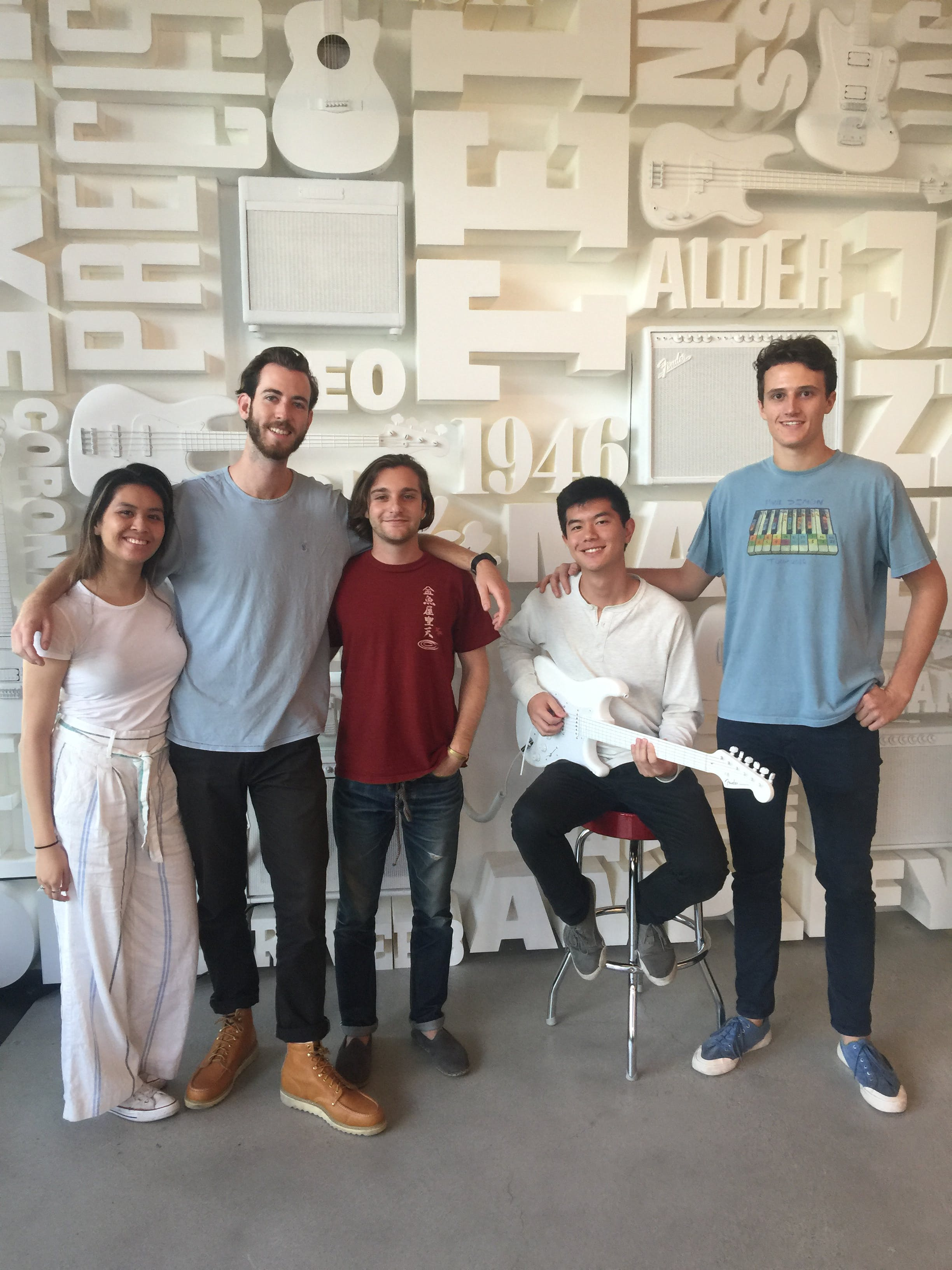 4 students standing in front of a wall of white guitars, one male sitting on stool holding white guitar