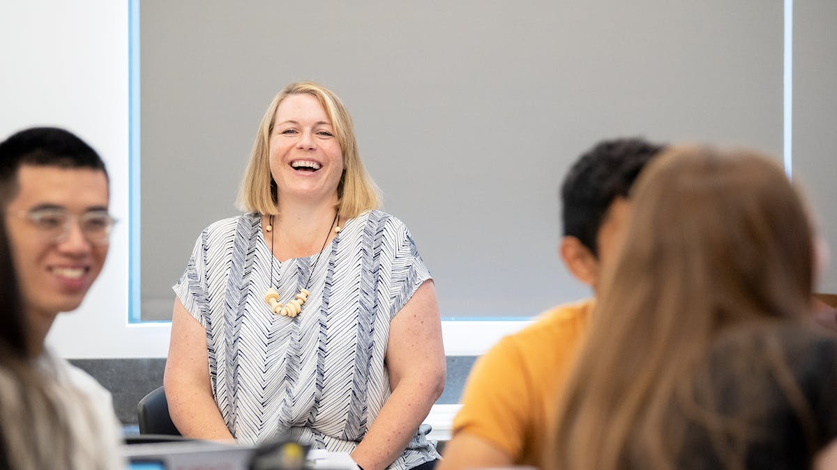 Female professor laughing with students