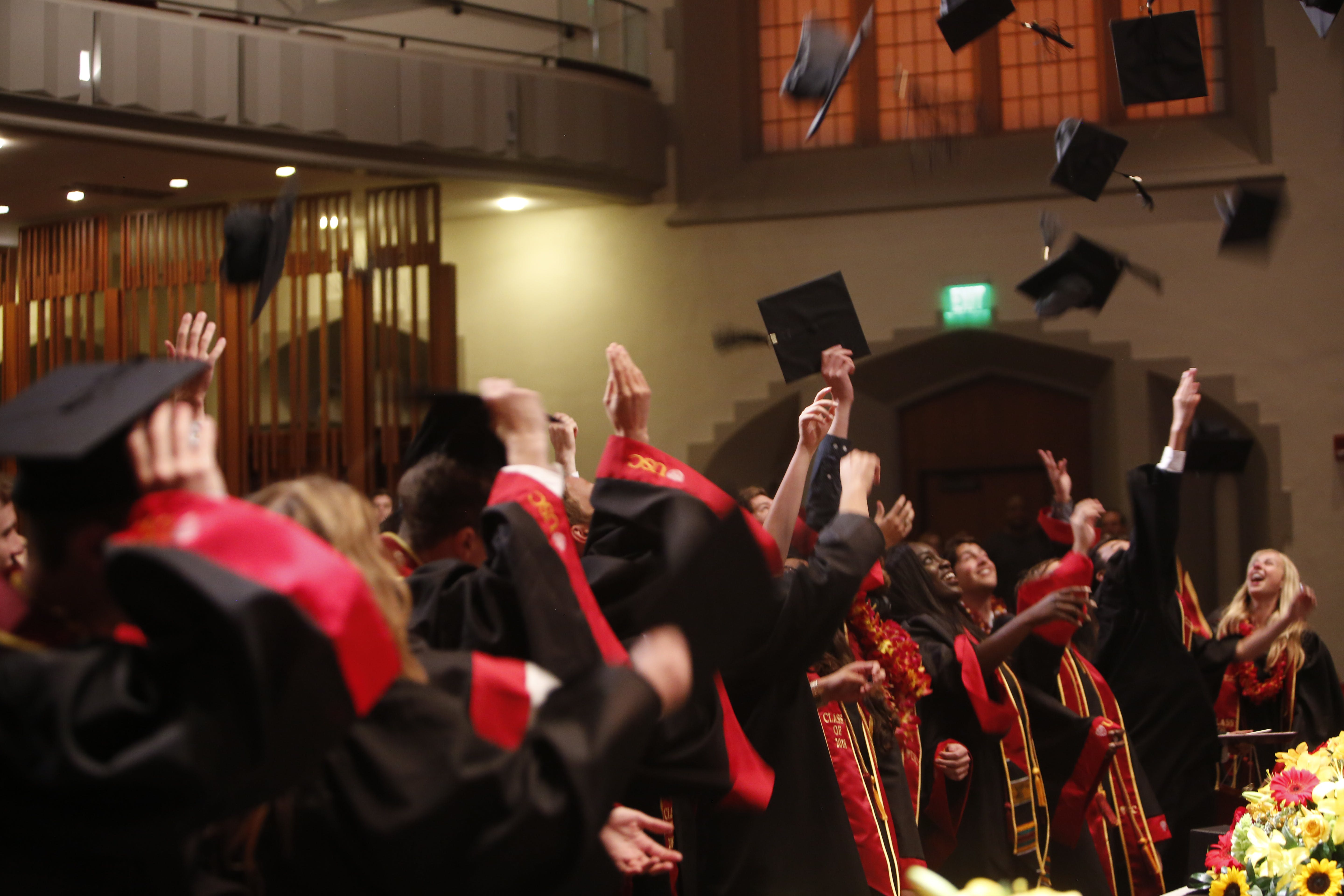 Graduating students wearing cap and gown throw caps into the air