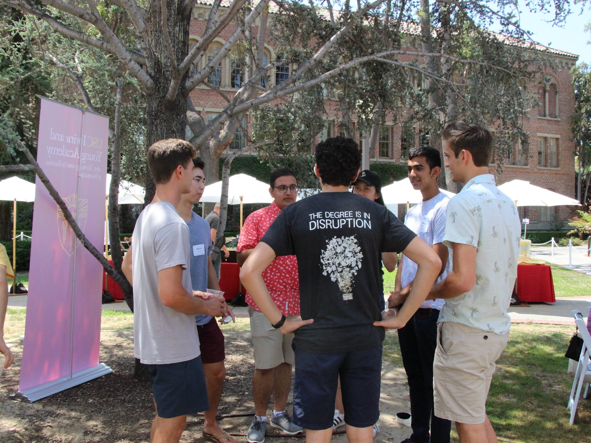 """A gathering of students. One wears a t-shirt that reads """"The Degree is in Disruption"""""""