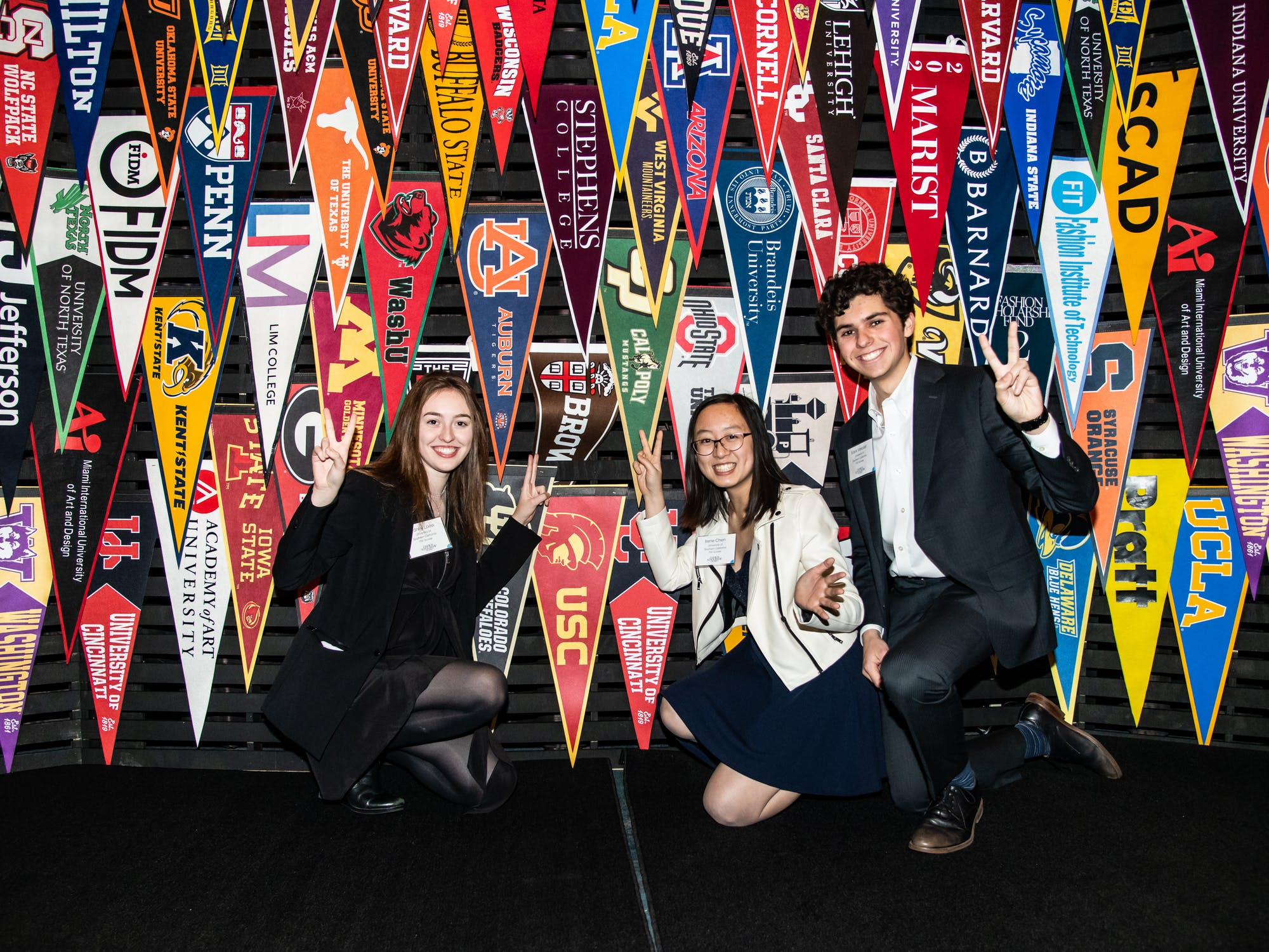Students standing in front of a wall of school flags