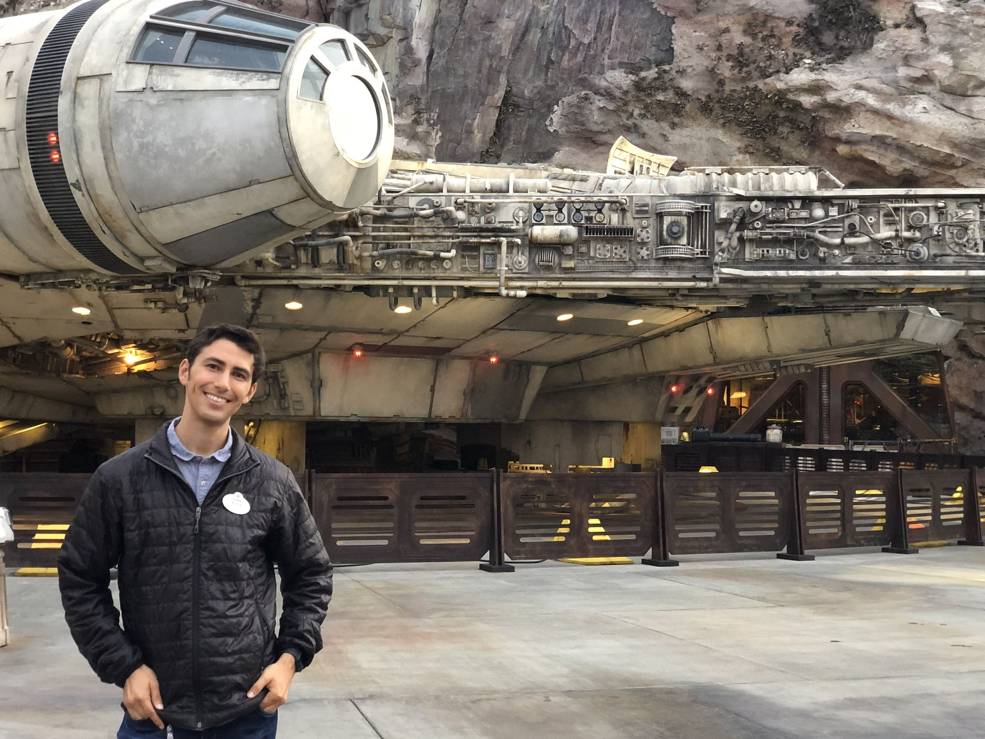 A young man smiles next to a Disneyland recreation of the Millennium Falcon from Star Wars