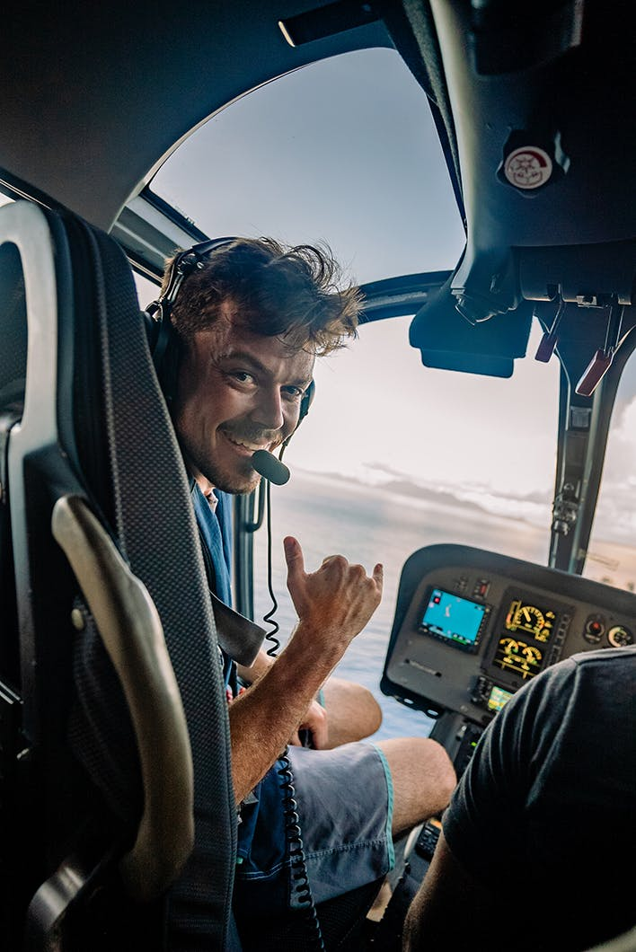 Smiling male seated at helicopter cockpit