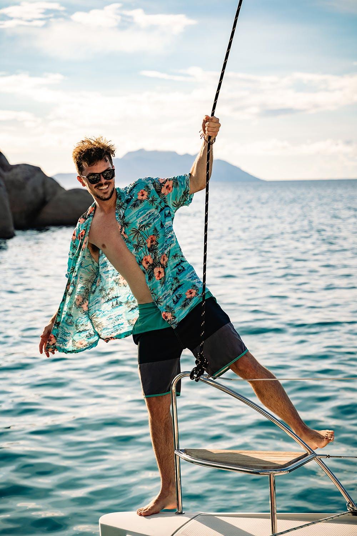 Male wearing hawaiian shirt standing on edge of sailboat