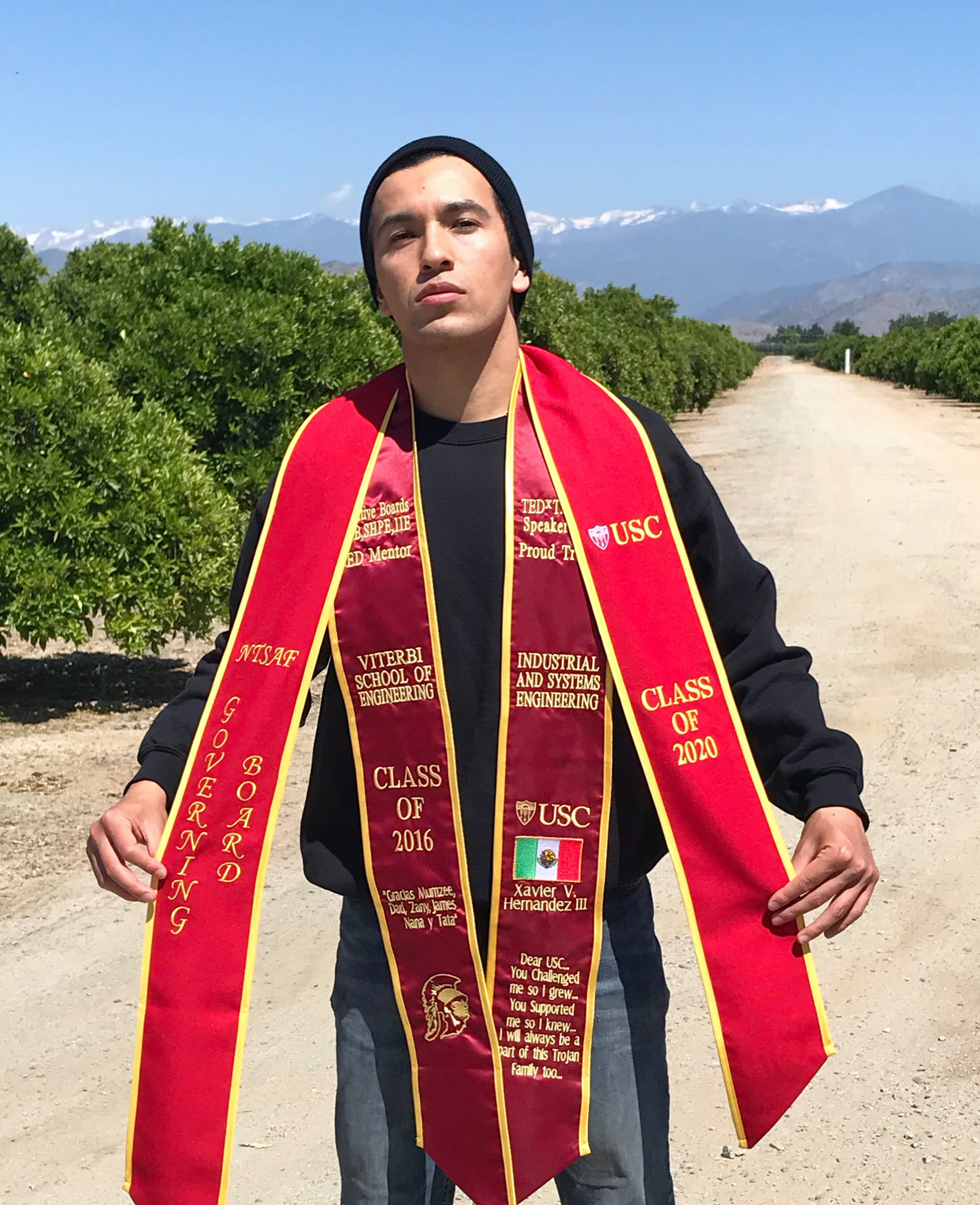 Graduating male with 2 red sashes