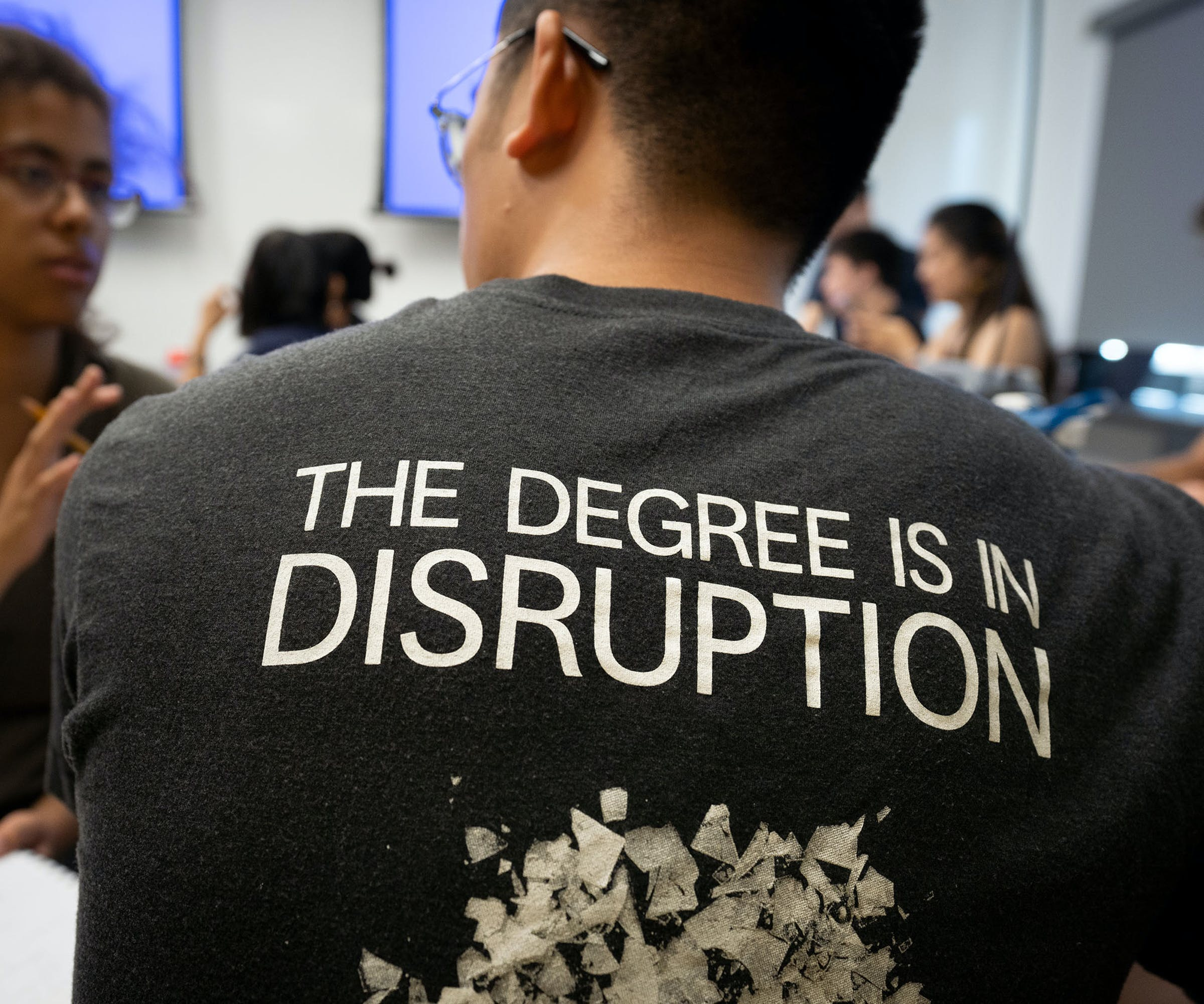 Two students, shirt says the degree is in disruption.