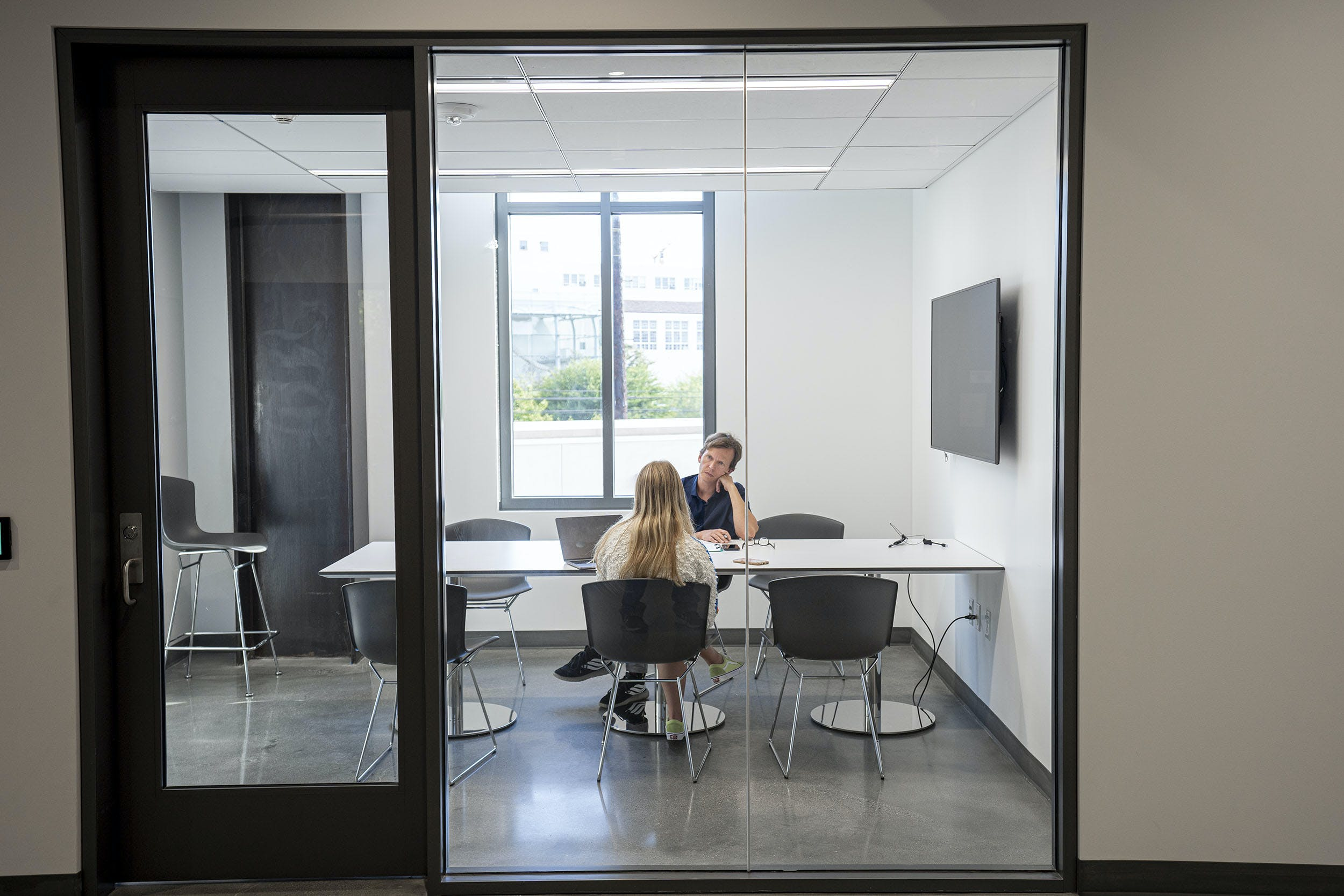 A student meets with a teacher in a conference room