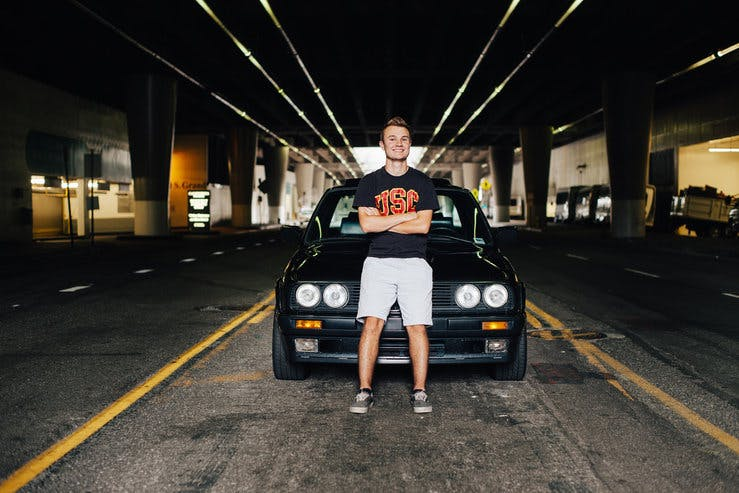 A young man in a USC shirt sits on the hood of a black car parked in the middle of an empty street under a bridge.