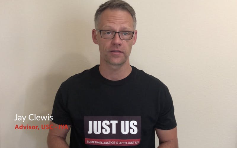 """Jay Clewis wears a shirt that says """"JUST US"""""""