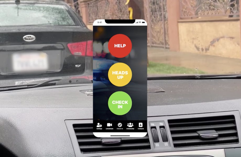 """An AR interface superimposed over a car dashboard. The interface has a traffic-light red/yellow/green light structure and reads """"Help,"""" """"Heads Up"""" and """"Check In"""""""